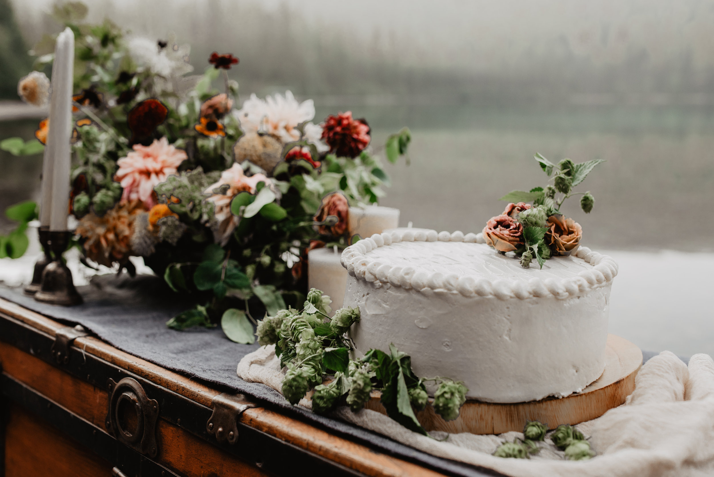 Beautiful vintage chest with displayed locally sourced sustainable flower arrangements and organic simple wedding cake on top