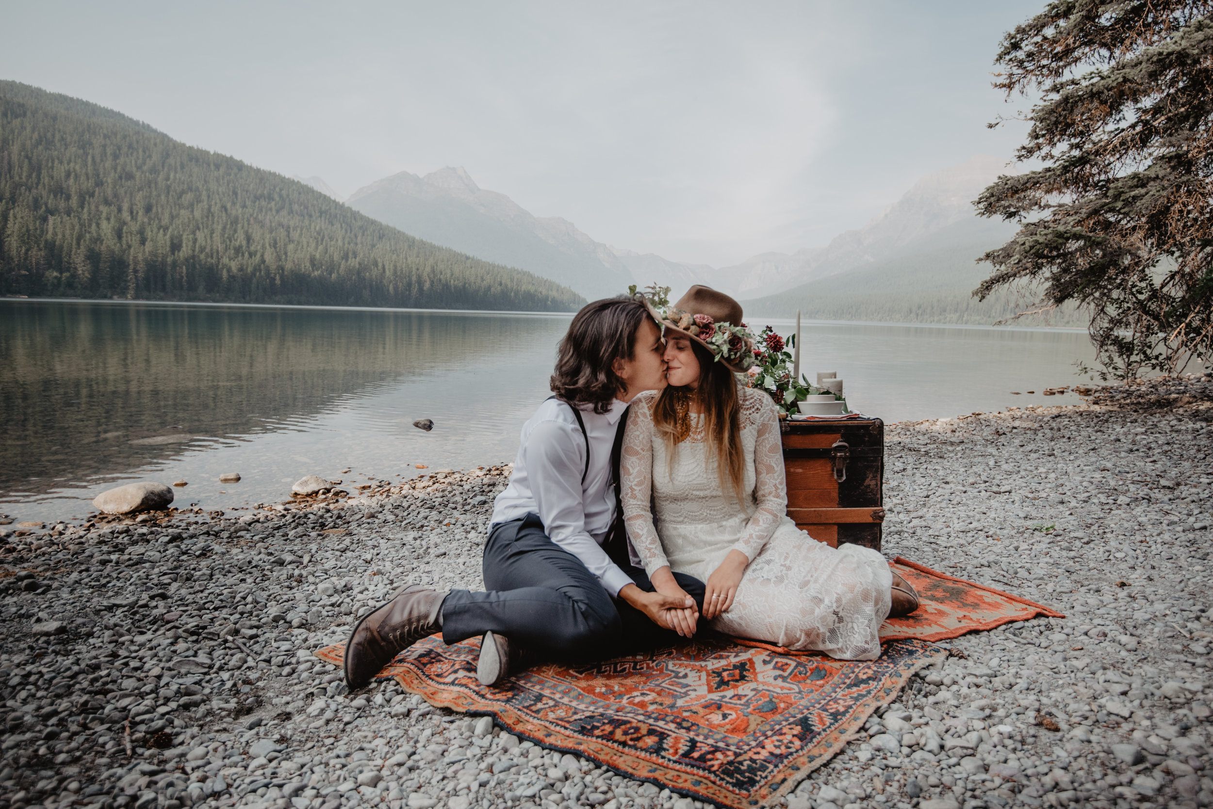 Outdoor portrait of beautiful couple wearing bohemian and vintage suit and lacey wedding dress while kissing at the Glacier National Park