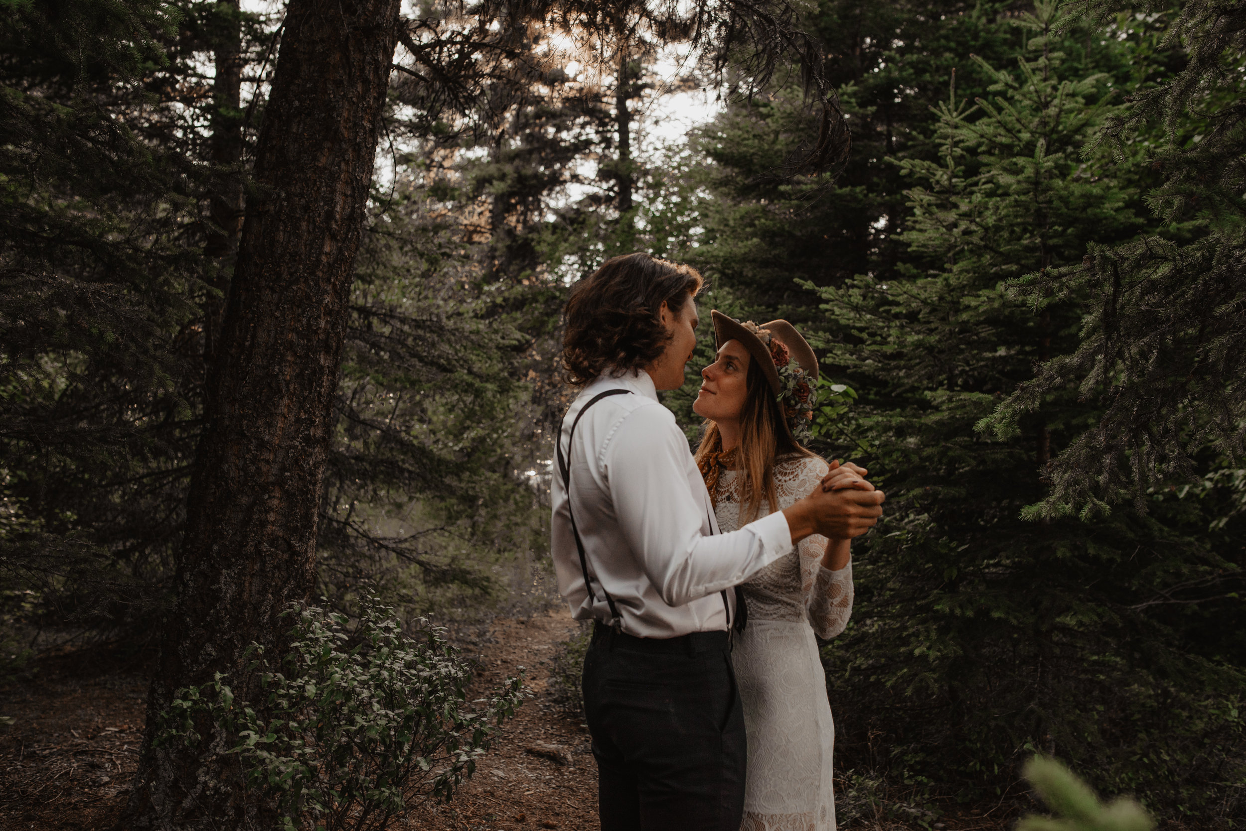 Outdoor portrait of beautiful couple wearing bohemian and vintage suit and lacey wedding dress dancing at the Glacier National Park