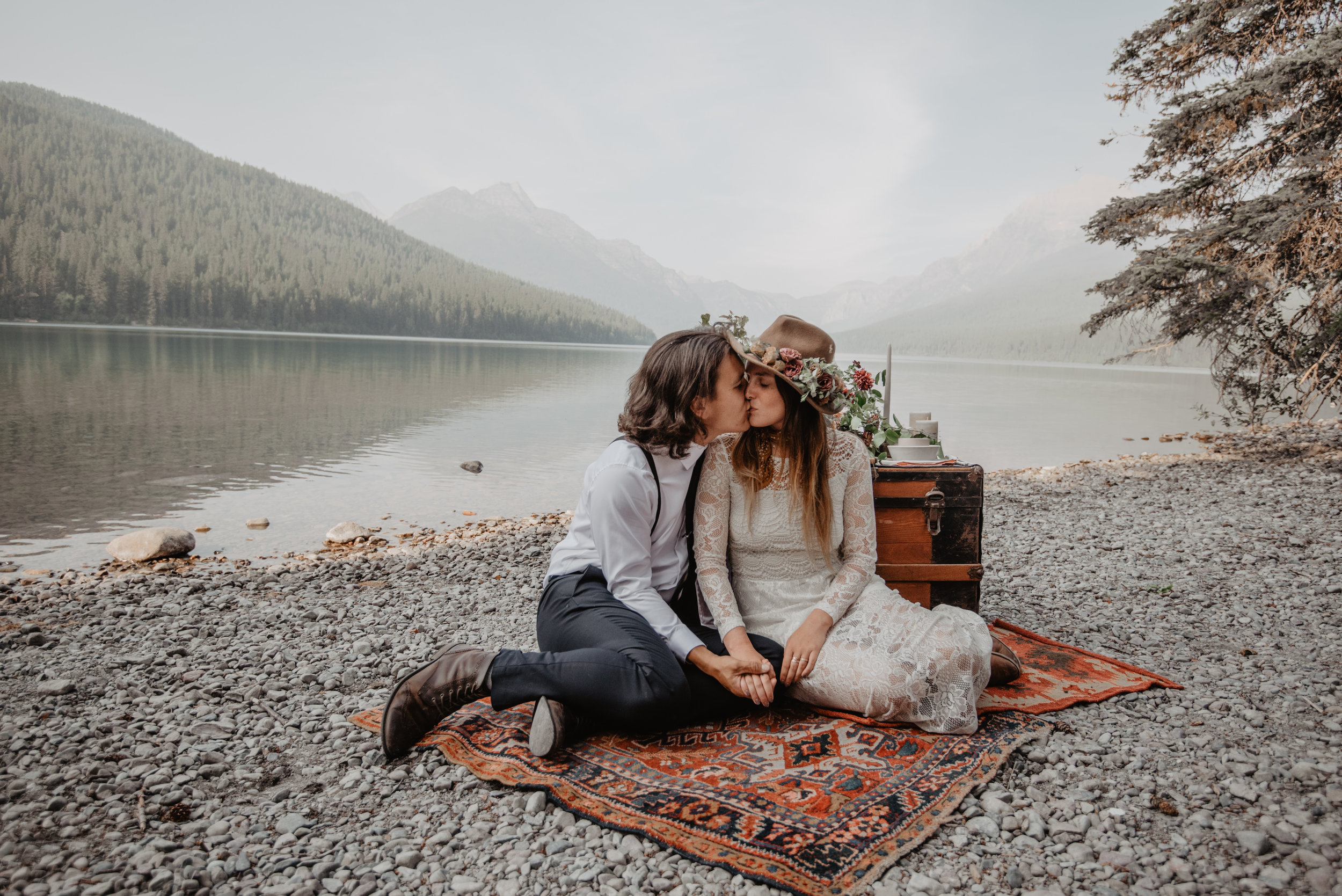 Outdoor elopement portrait of engaged couple sitting on renewable and sustainable bohemian carpet while kissing each other at Glacier National Park MT