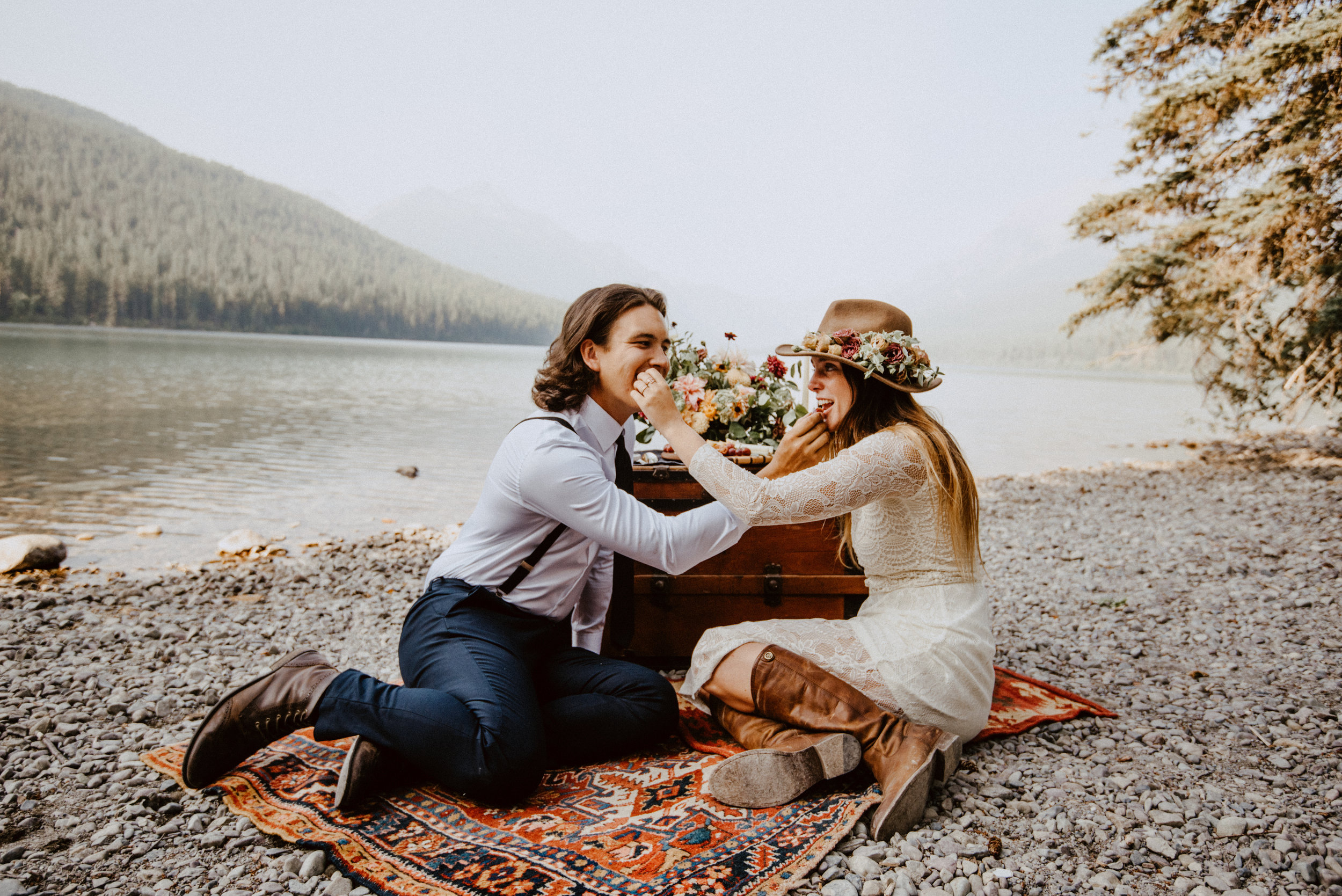 Outdoor elopement portrait of engaged couple sitting on renewable and sustainable bohemian carpet while feeding each other at Glacier National Park MT