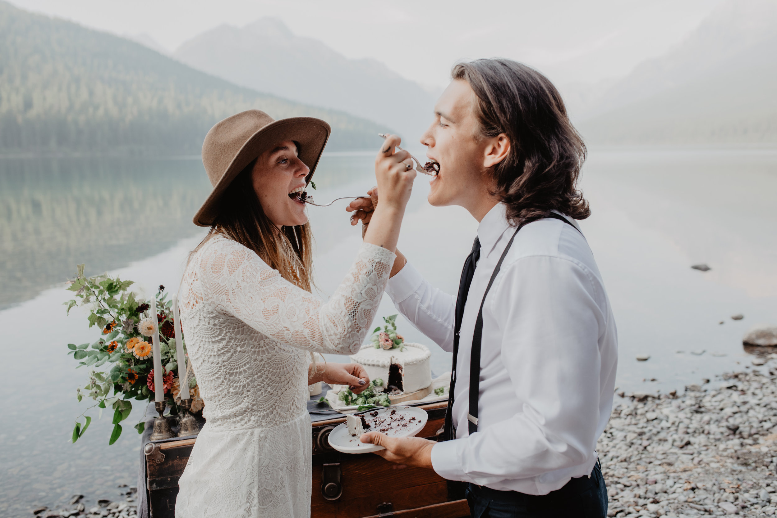 Outdoor elopement portrait of engaged couple feeding each other organic wedding cake at Glacier National Park MT