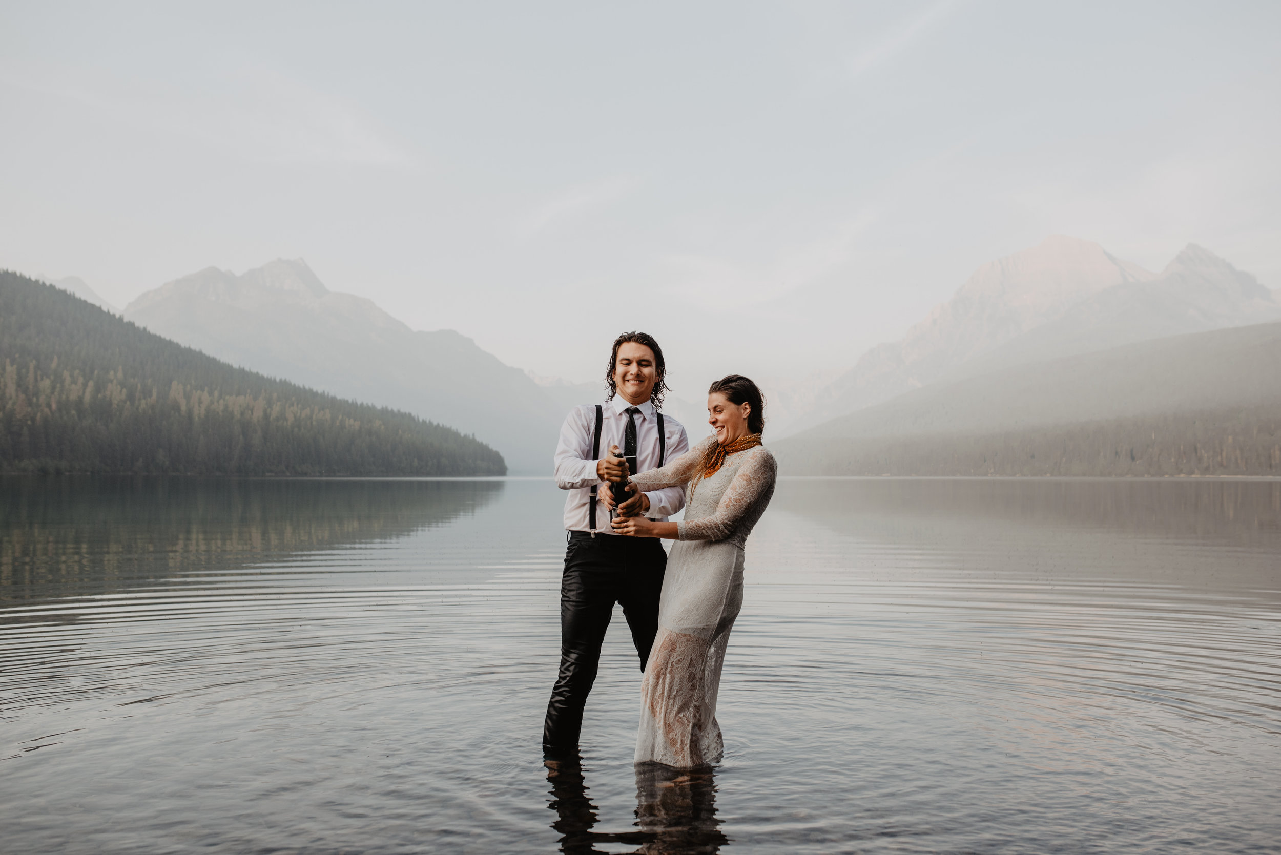 Outdoor elopement portrait of engaged couple poping champagne while in water at Glacier National Park MT