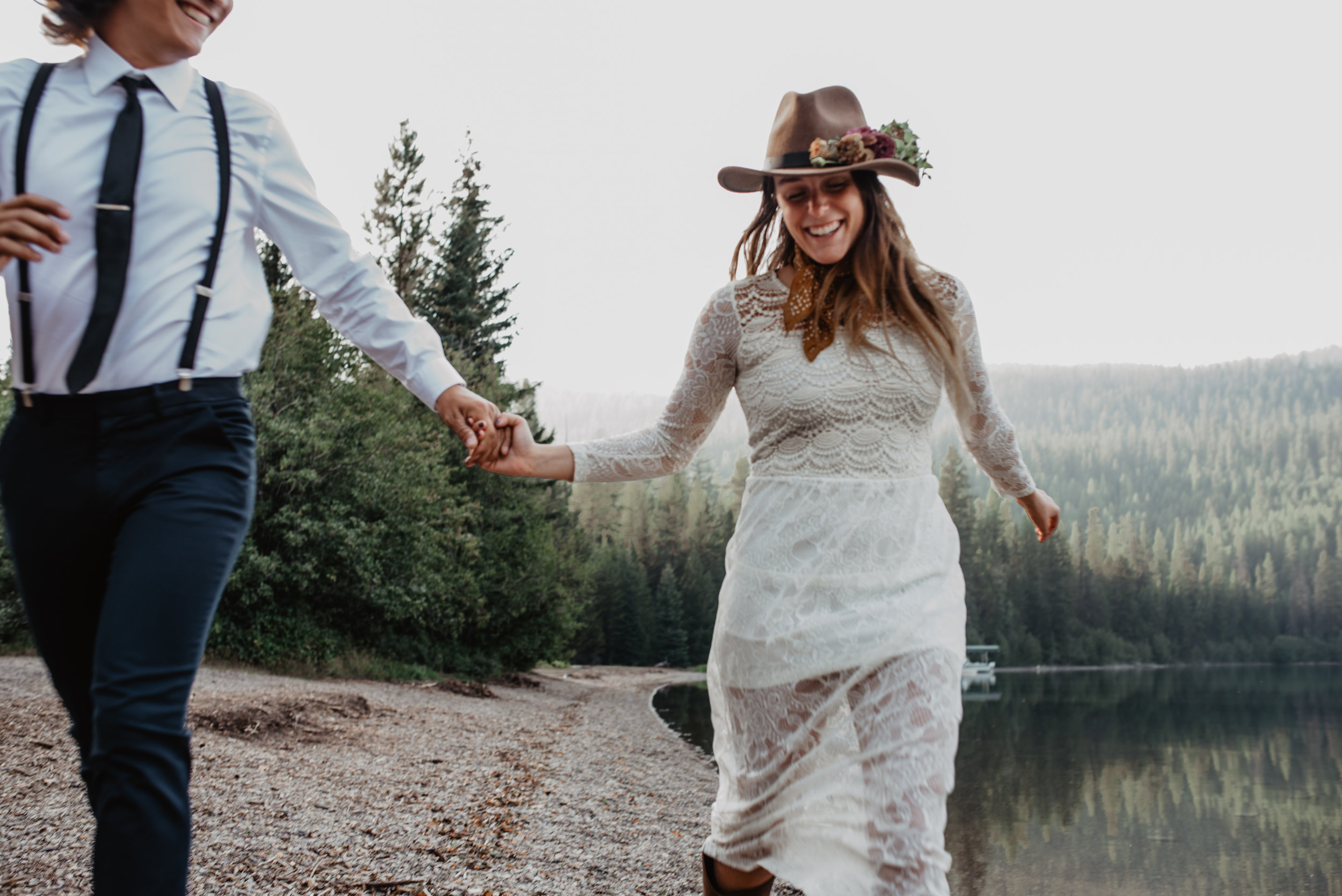 Outdoor sustainable elopement photo shoot of happy engaged couple holding hands at Glacier National Park MT