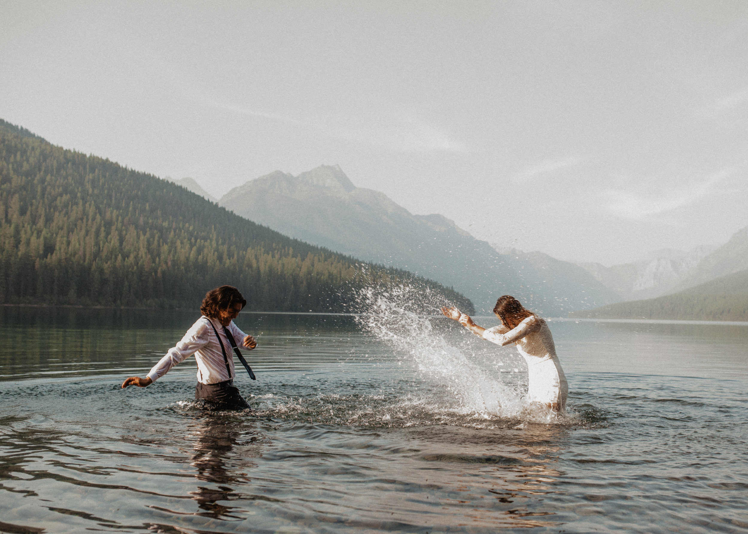 Outdoor elopement portrait of engaged couple splashing in water at Glacier National Park MT