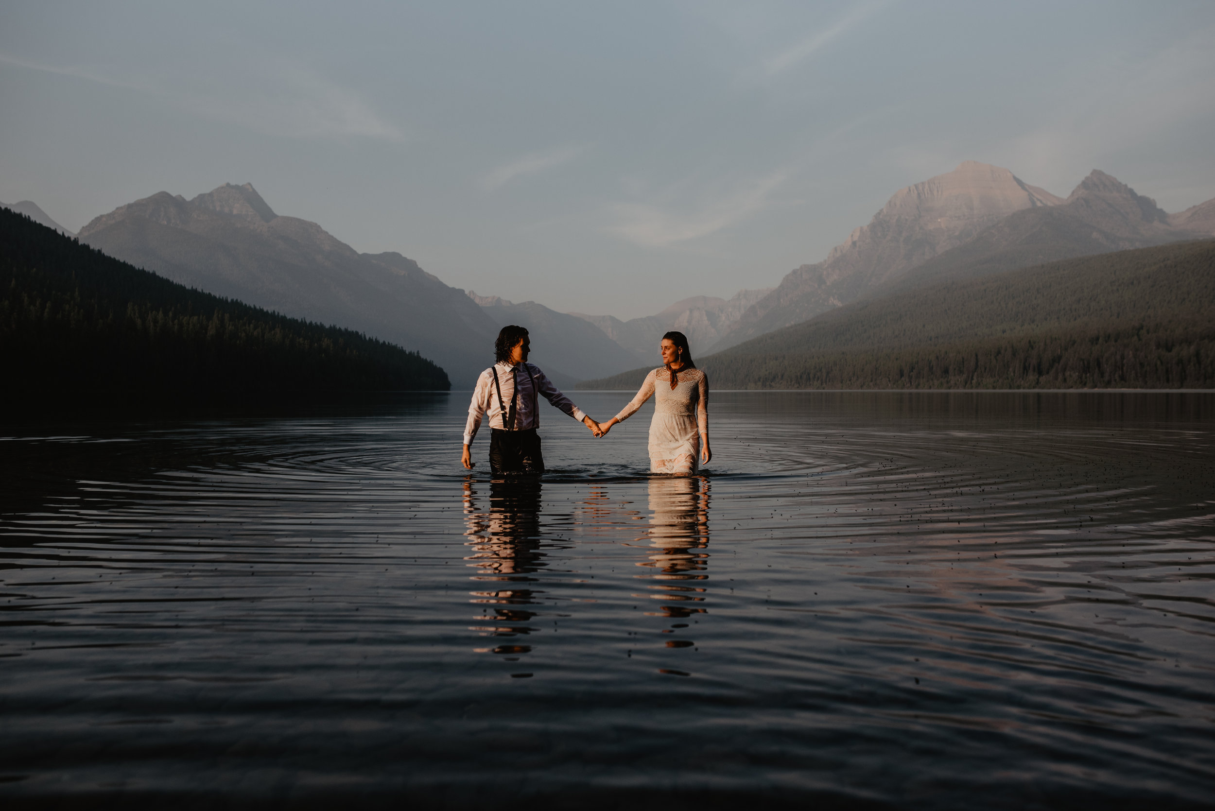 Outdoor elopement portrait of happy engaged couple holding hands in water at Glacier National Park MT