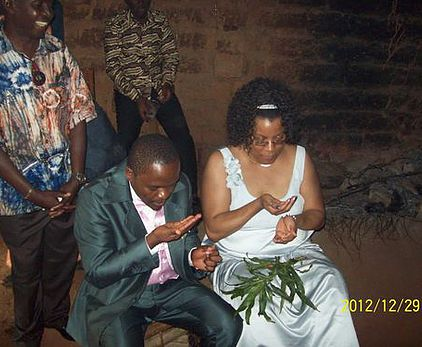 Yvette and her husband Constantin during their traditional wedding in his Cameroonian village, eating dimdim (a small seed).