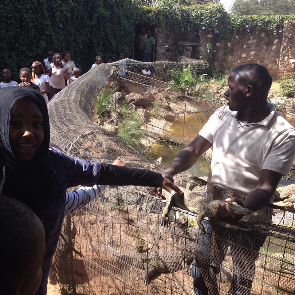 Pamela's daughter Naima touching a baby crocodile at Mambo Village in Kenya.