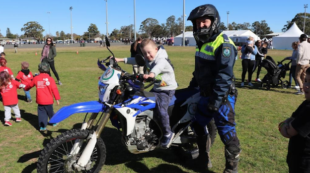 Cobi Graham, 7, of South Penrith sits on top of officer Andrew Hayward's police trail bike at NAIDOC celebrations in Jamison Park, Penrith on Friday. Picture: Danielle Jarvis