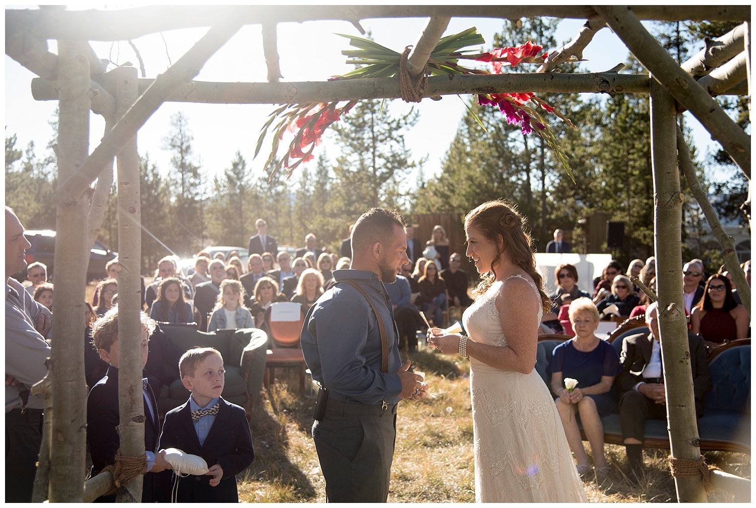 Couple Holding Hands Under Wooden Altar | Carolyn and Shawn's Wild Horse Inn Wedding at Devil's Thumb Ranch | Fraser Colorado Photography | Farm Wedding Photographer | Apollo Fields Photojournalism