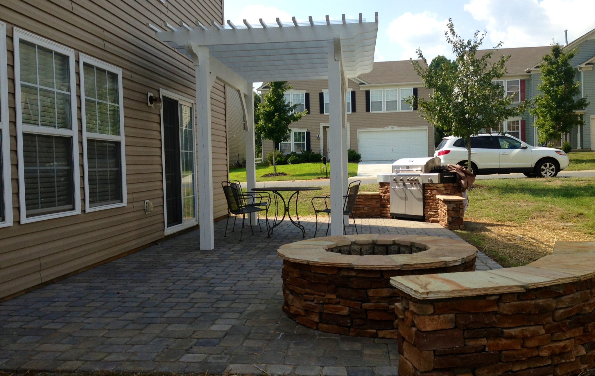 A Paver Patio with new seating bench and fire pit for your family and kids to enjoy during a nice summer night.