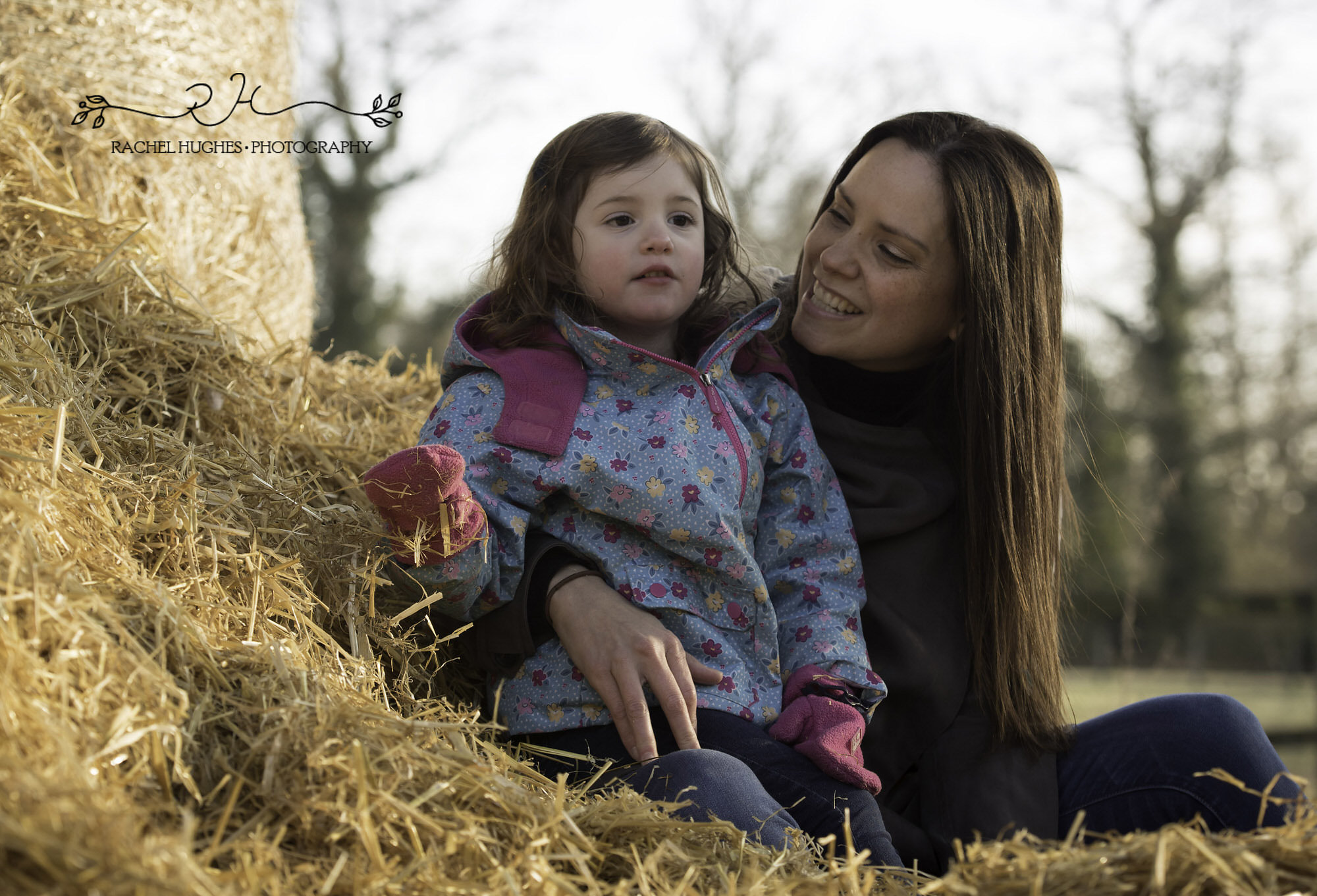 Girl and mummy in sunset haystack