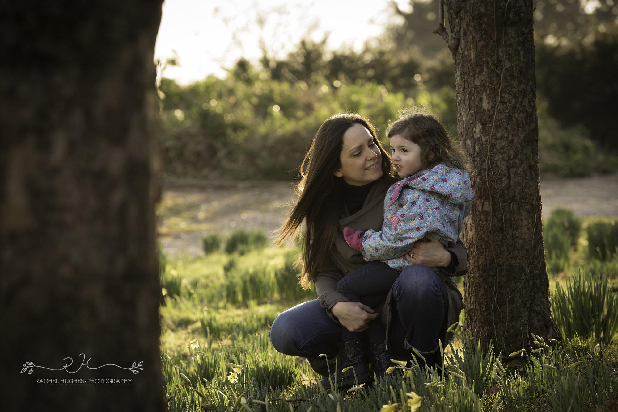 Girl cuddling mummy in orchard