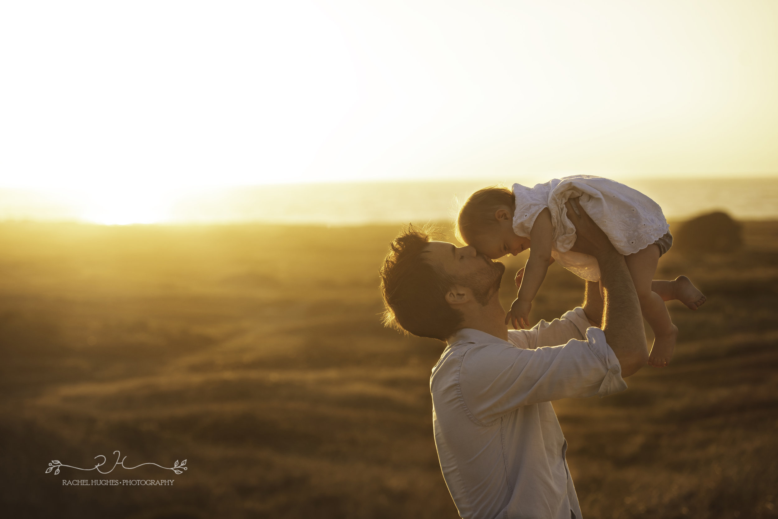 Jersey photographer - father kissing baby at sunset
