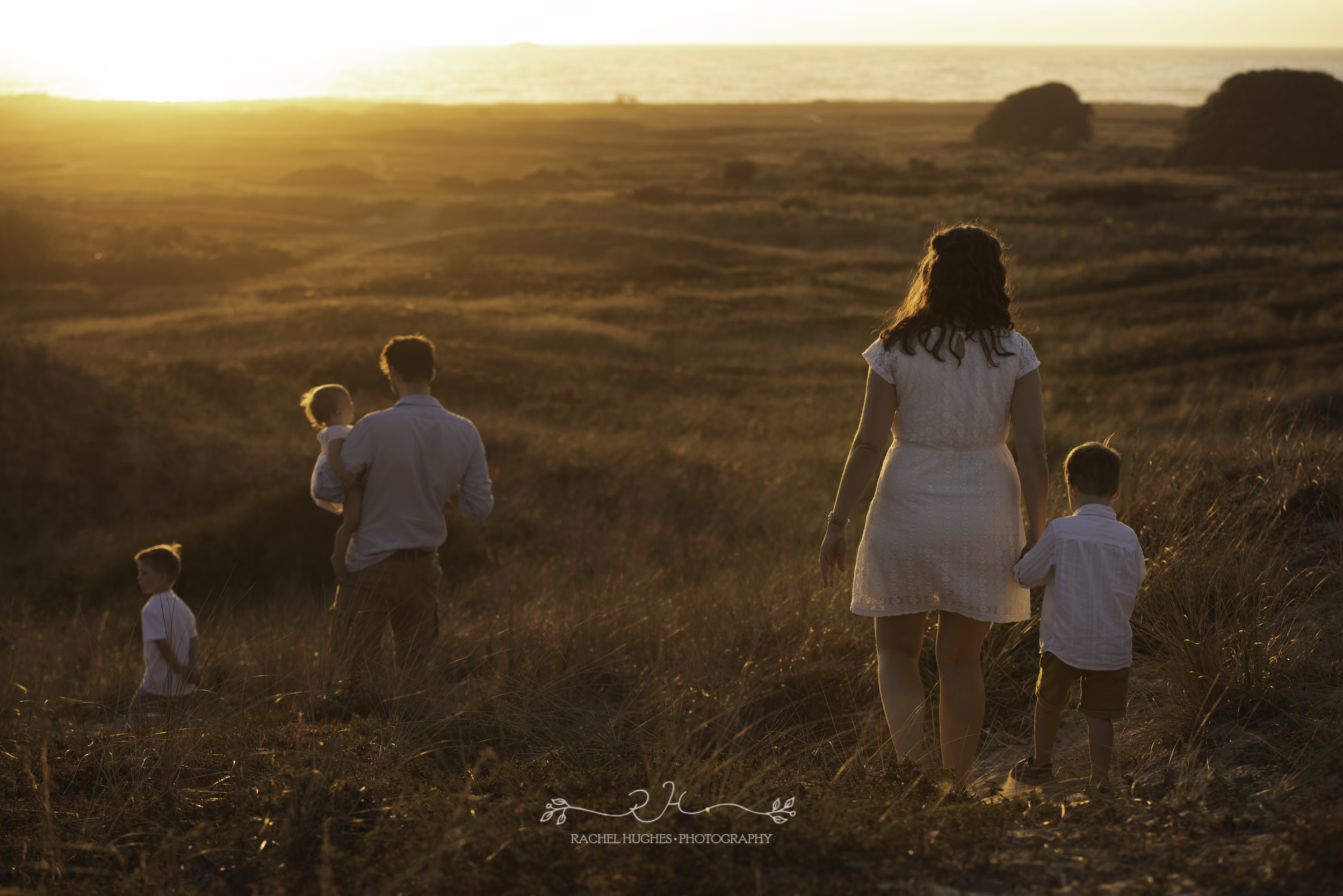 Jersey photographer - family walking into St Ouen's sunset
