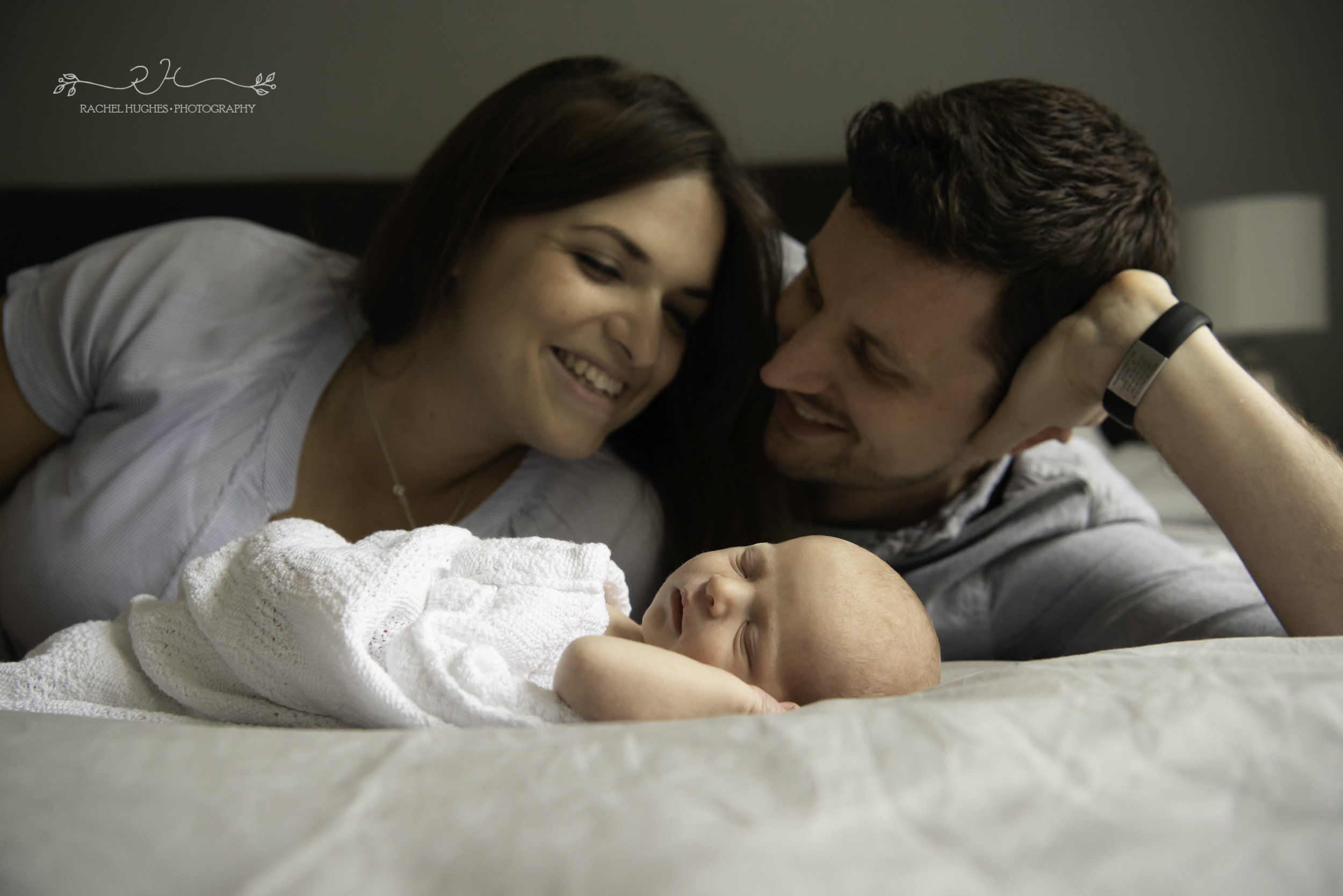Jersey photographer - parents on bed with newborn