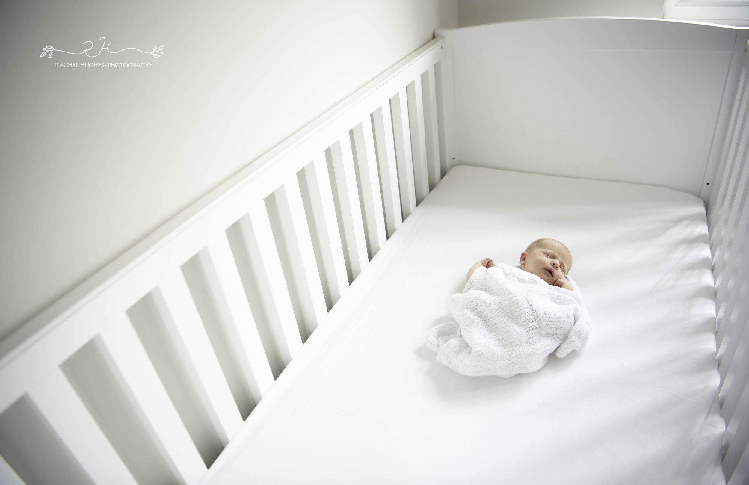 Jersey photographer - tiny newborn in cot