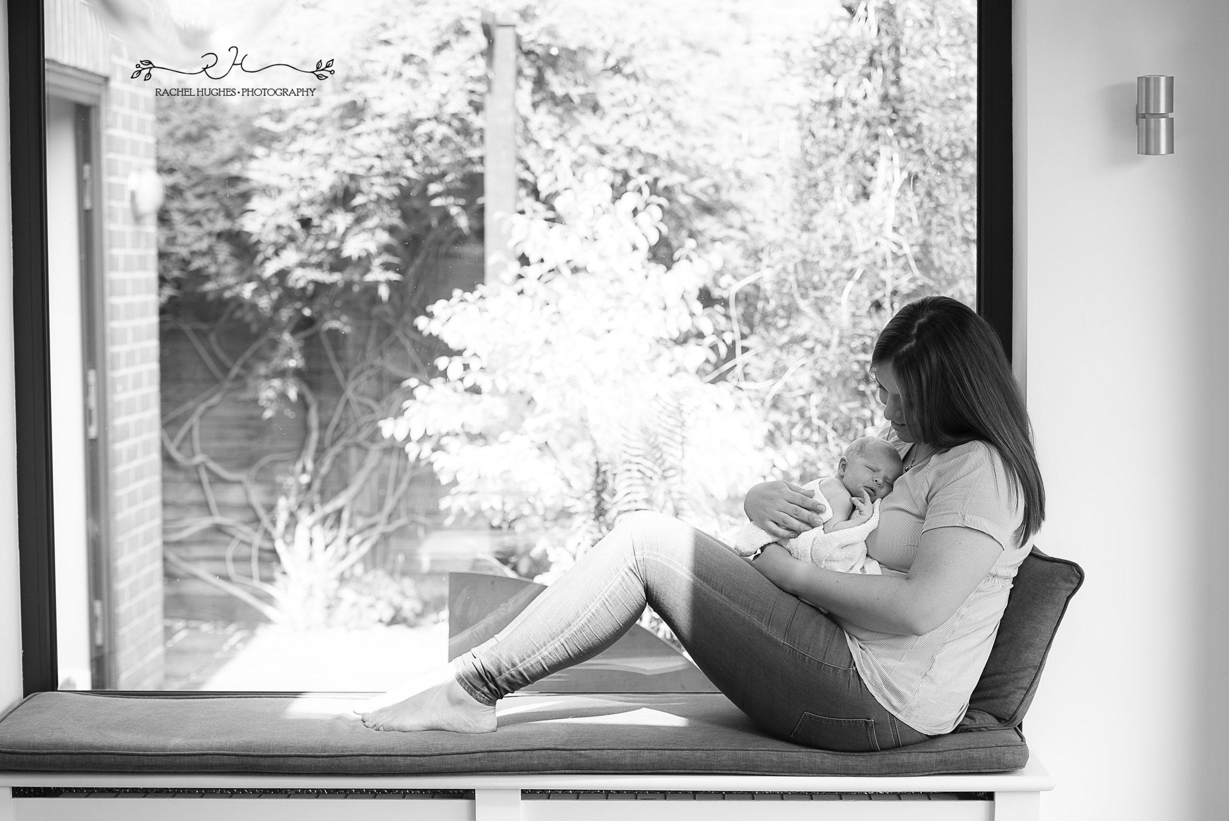 Jersey photographer - mum and newborn in window at home