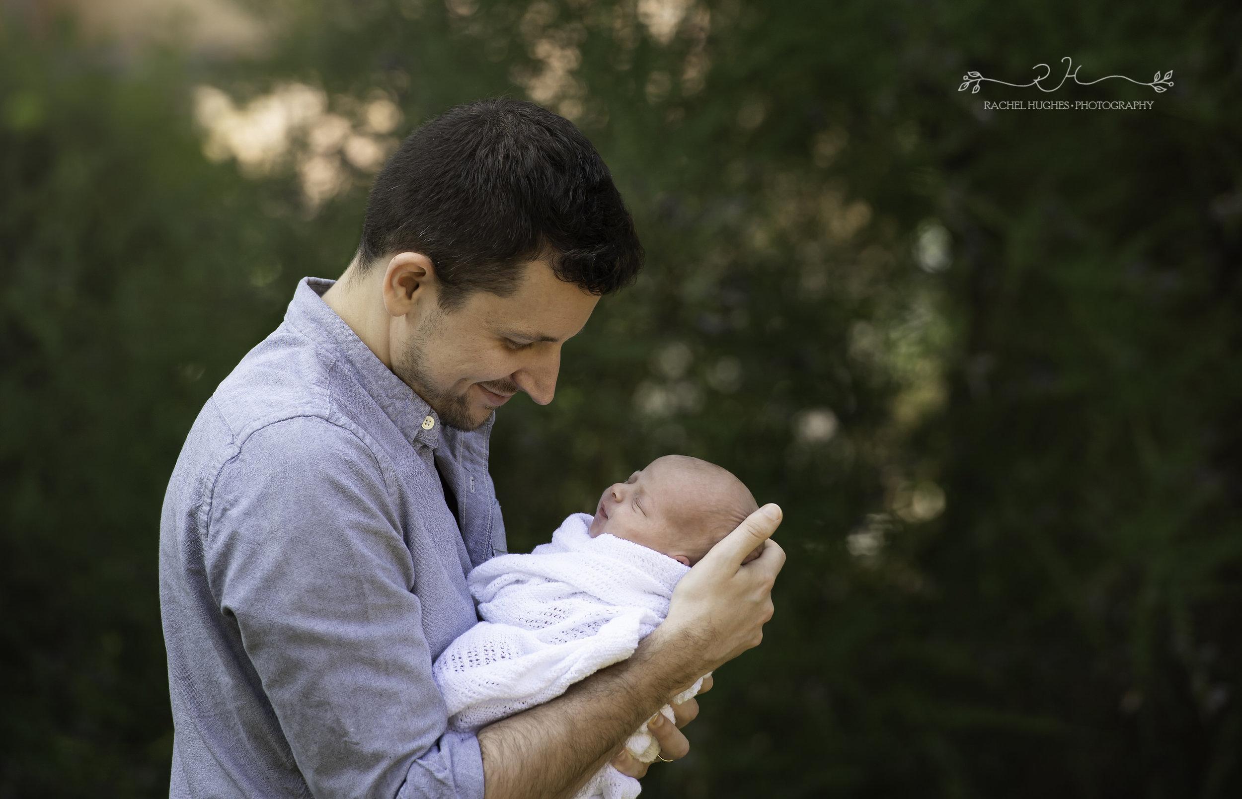 Jersey photographer - newborn baby in Daddy's arms in garden