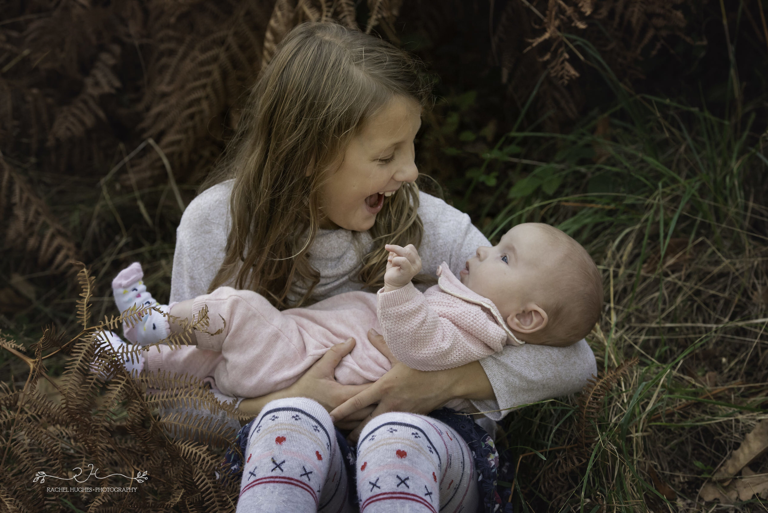 Jersey photographer - sister laughing with new baby