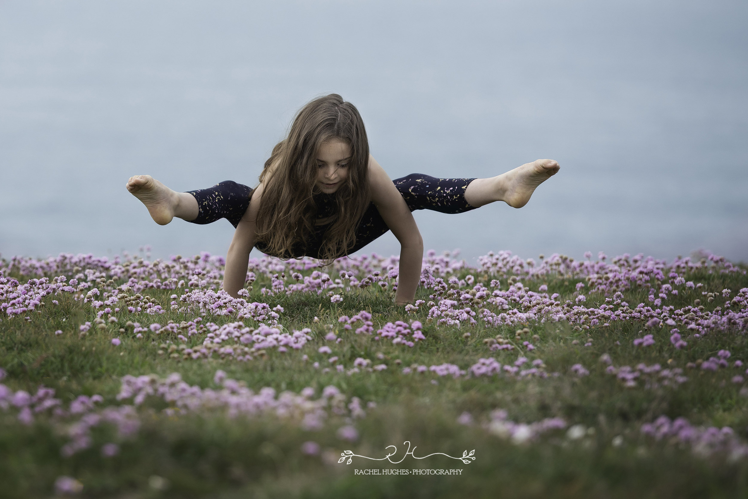 Jersey photographer - gymnast balancing in sea pink flowers