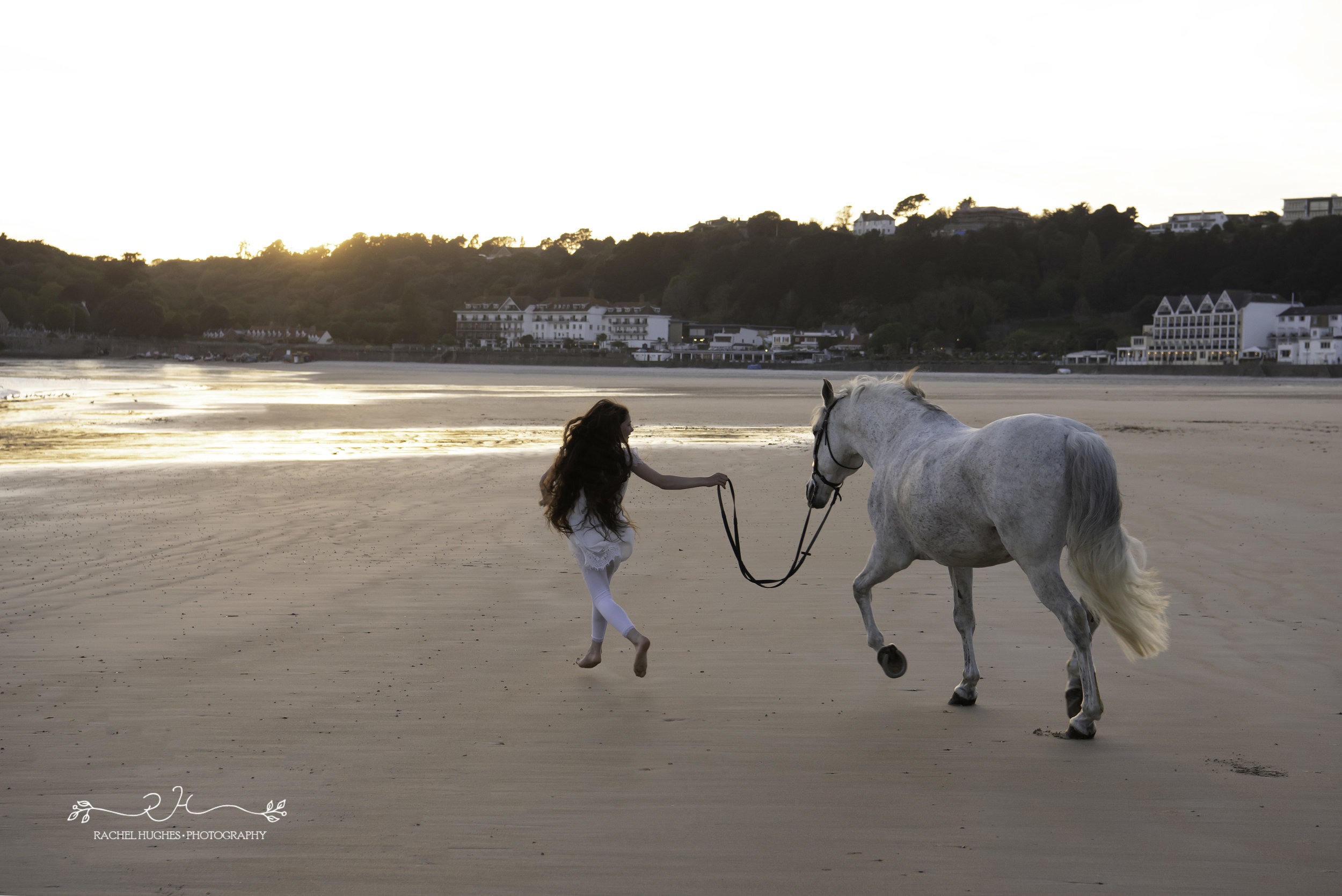 Jersey photographer - girl and horse skipping on beach