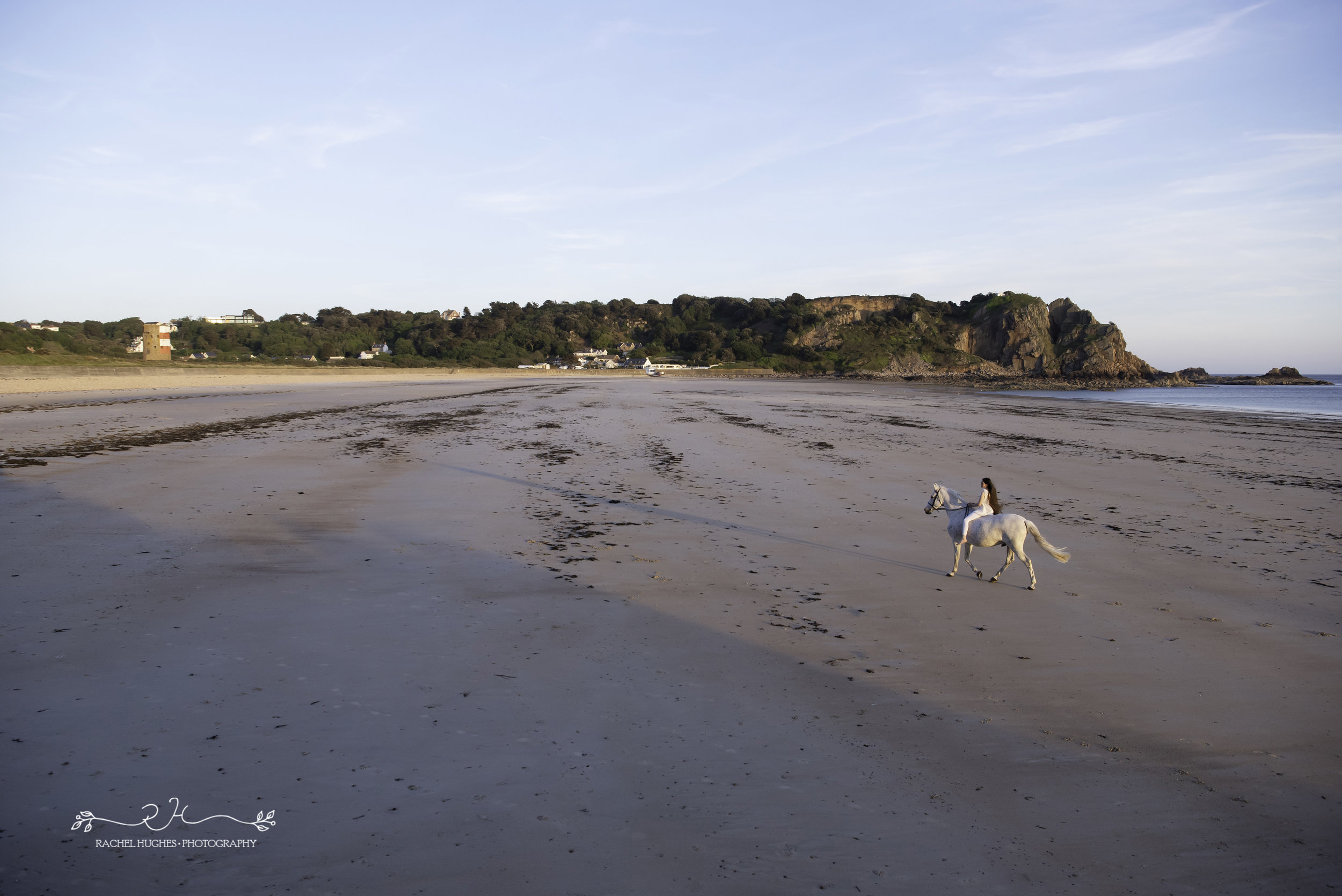 Jersey photographer - girl riding white horse at Ouaisne Bay