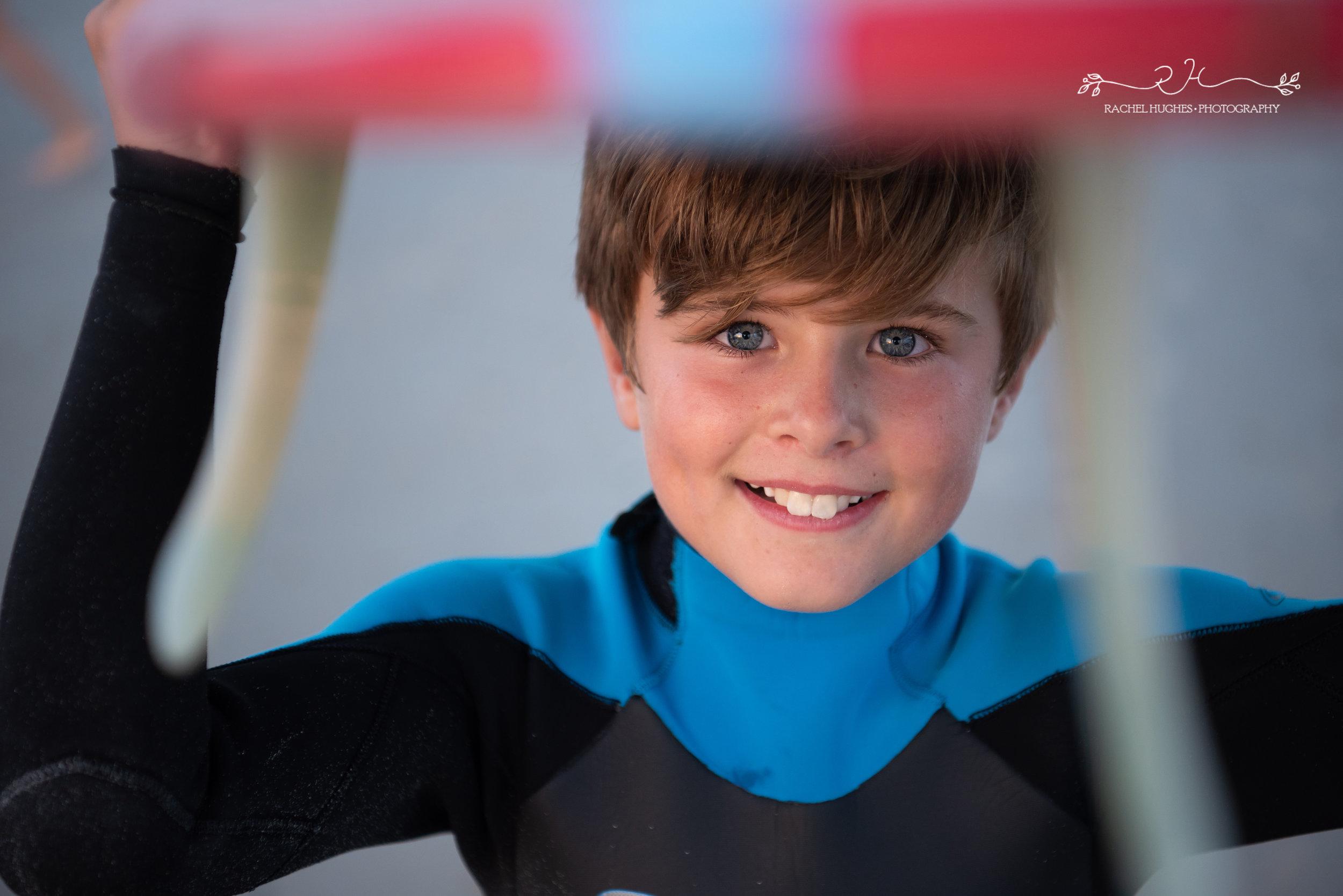 Jersey photographer: boy looking through surfboard