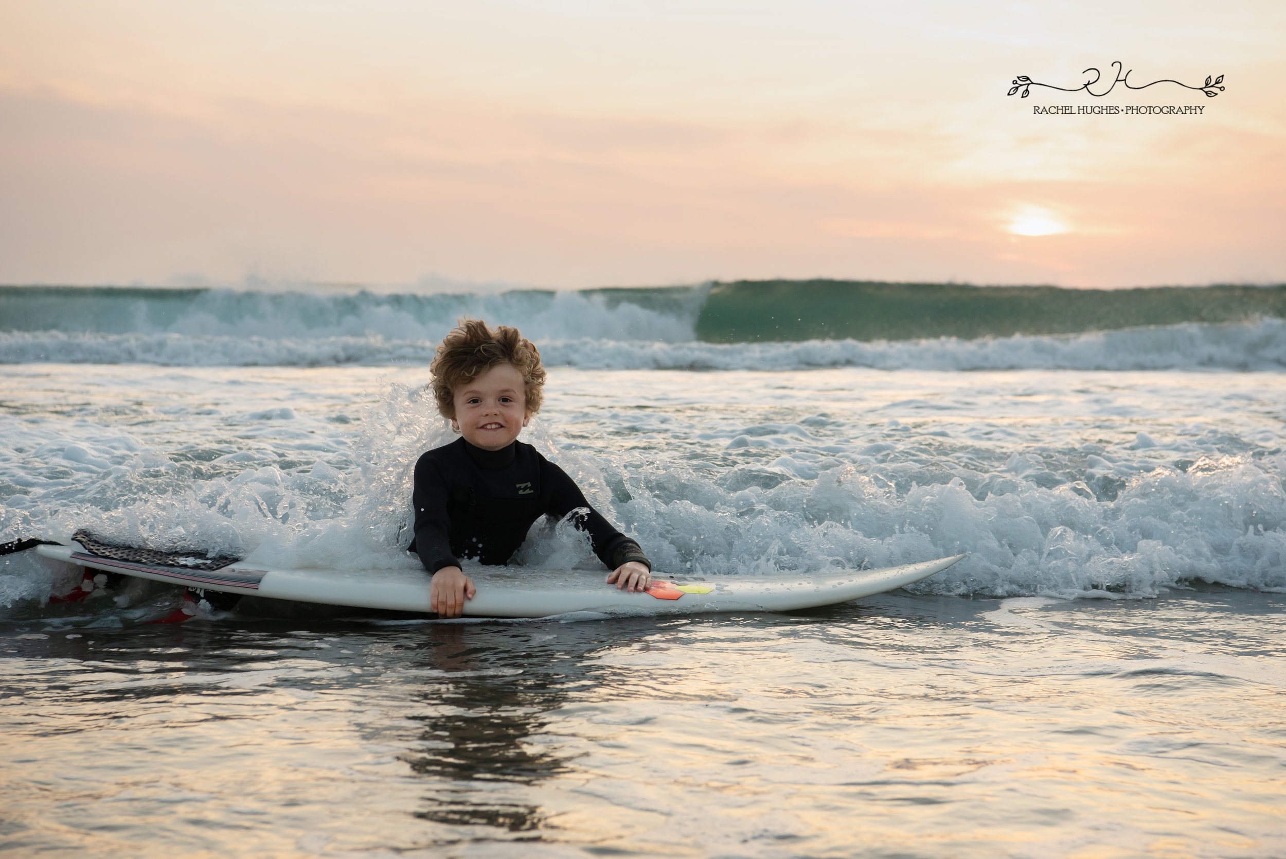 Jersey photographer - boy splashing in waves with board