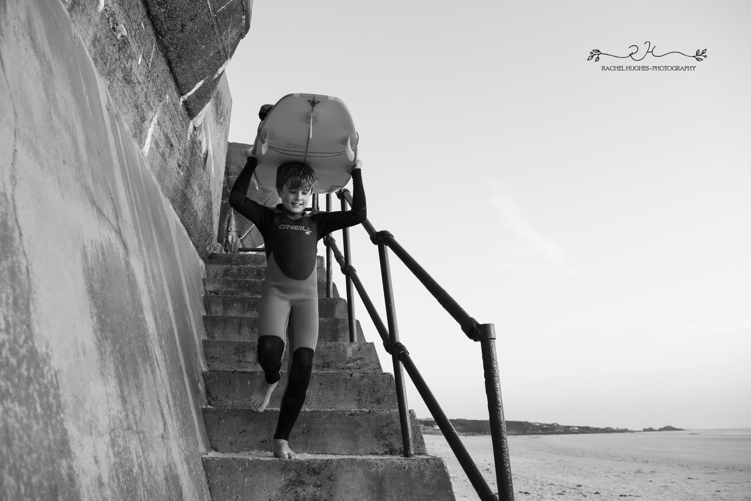 Jersey photographer - boy carrying surfboard down steps