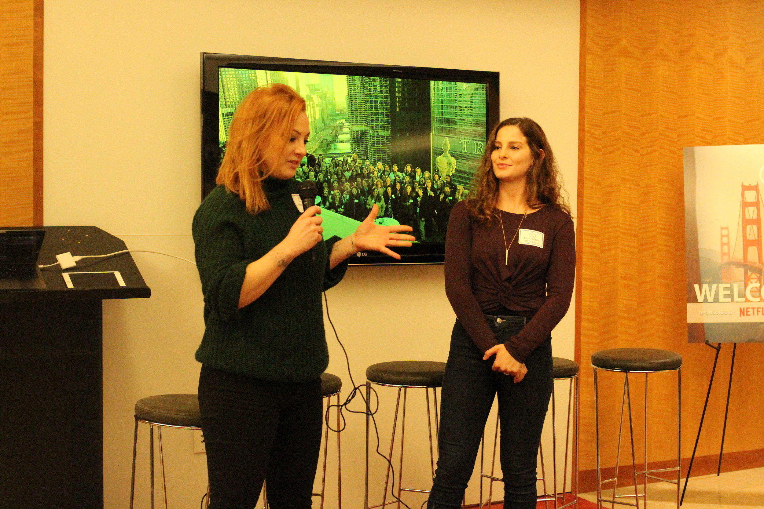 Rebecca Stanic speaking at the WTF NANOG 75 event with Nadia Tuffaha looking on in admiration.