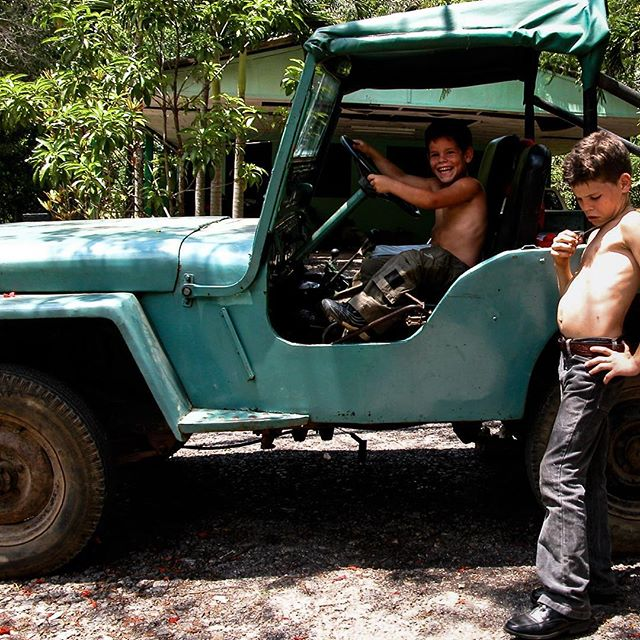 Two boys and jeep circa 2005. Juan Antonio's youngest threatens to drive to town on his own. It's rare in these parts of Cuba for farmers to have their own ride, still. #ruralcuba #diezañosdespues #kidsofcuba #trouble