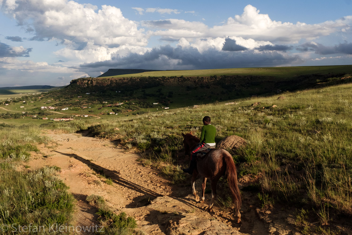 Thabo, 13, rides one of his father's seven horses through the mountainous landscape of Matatiele.