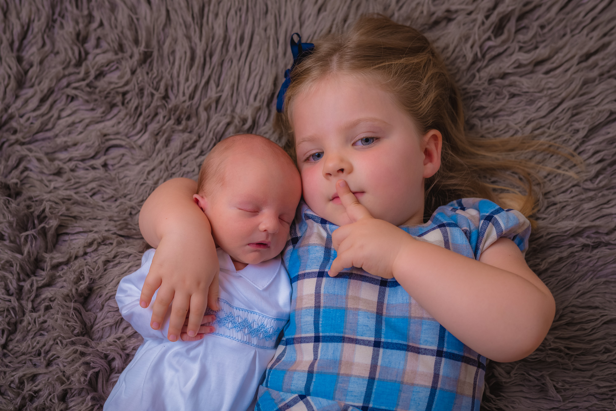 A young boy poses with her newborn baby brother.