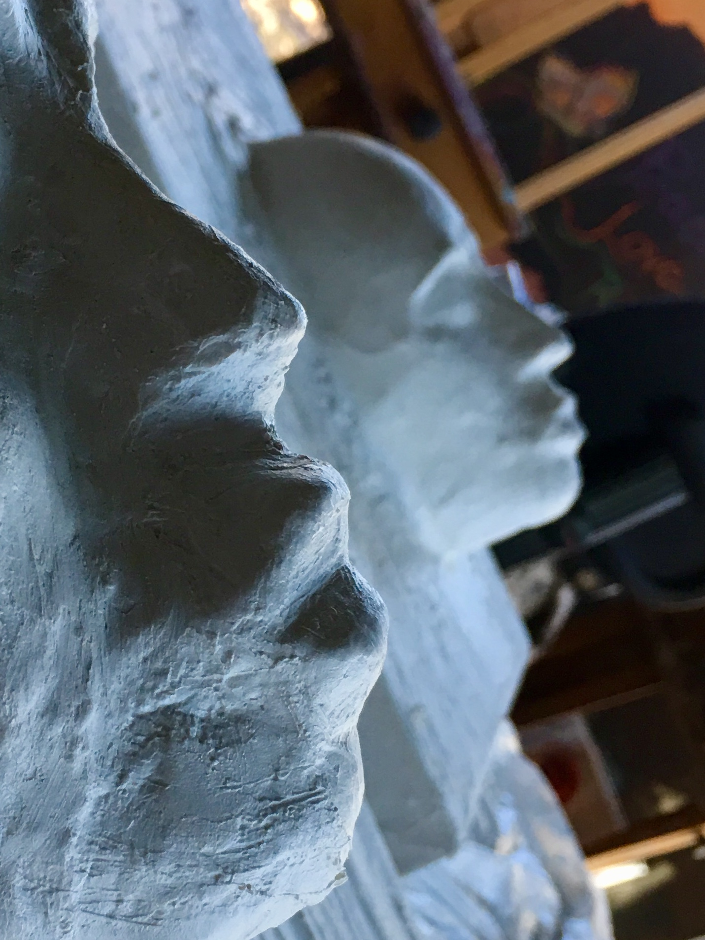 Plaster faces on canvas.