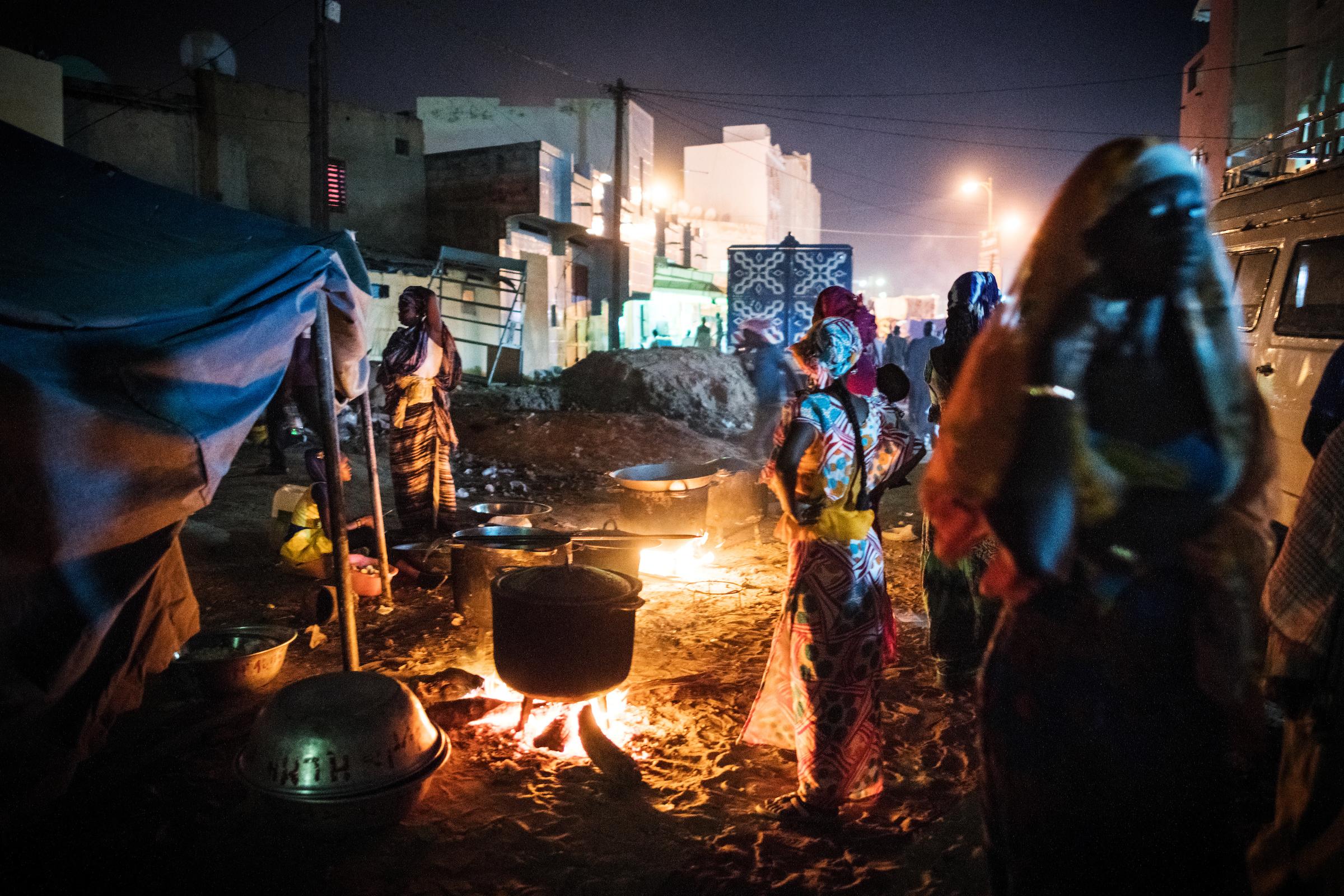 7. November 2017. In der Nacht vor dem Grand Magal Festival kochen Frauen in den Straßen von Touba traditionelle senegalesische Gerichte. Nach dem Willen von Amadou Bamba sollte jeder Gläubige, der zum Großmagal in Touba reist, kostenloses Essen und Unterkunft erhalten.