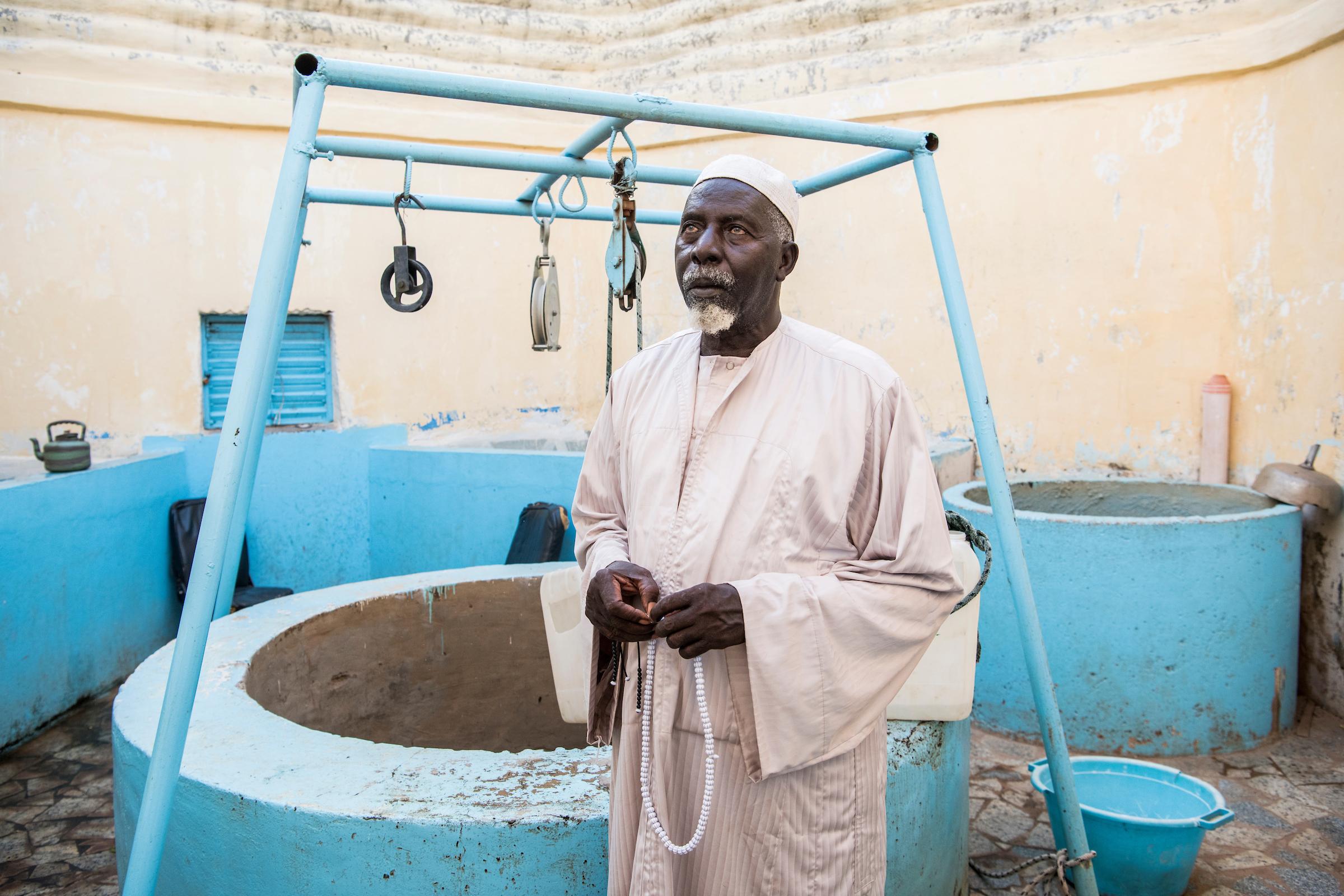 6. November 2017. Serigne Touba Khouma ist der Verwalter des Brunnens am Grab von Sokhna Mame Diarra Bousso, der Mutter von Amadou Bamba, die einen ähnlichen Status wie Maria für Christen hat. Wie in Lourdes erhoffen sich die Gläubigen Heilung, Kraft und Segen vom Weihwasser dieses Brunnens.