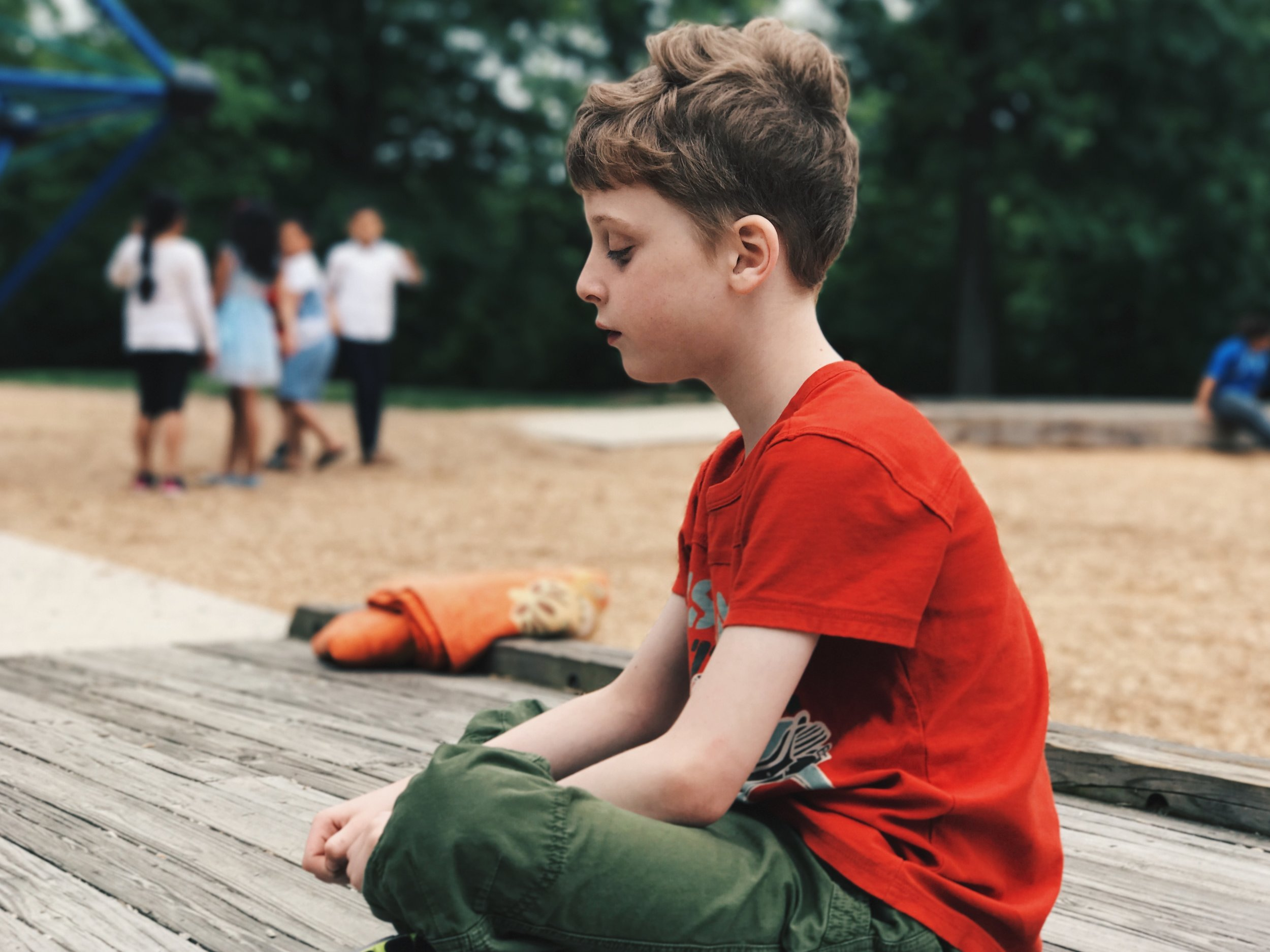 A young autistic boy sits quietly while children in the background gaze at him.