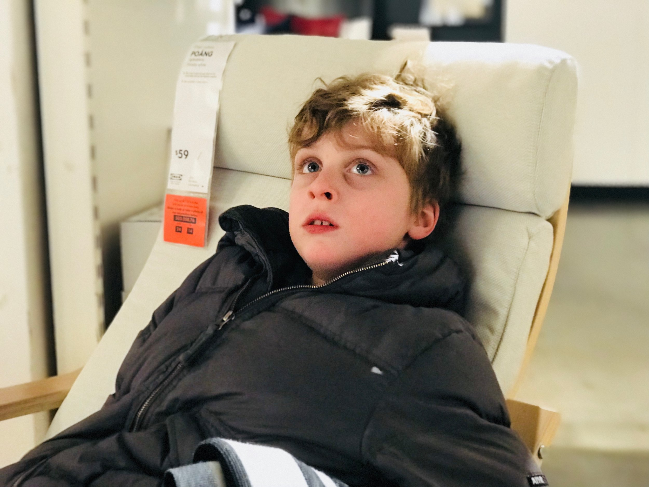 C, a young autistic boy, sits on a chair in an Ikea store, enjoying a relative moment of calm.