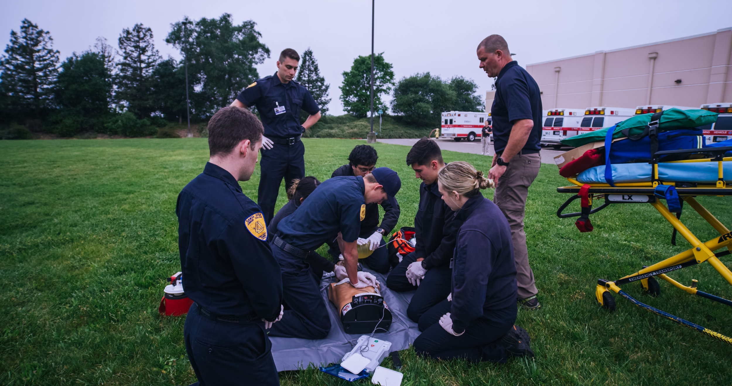 Students performing CPR on dummy in field