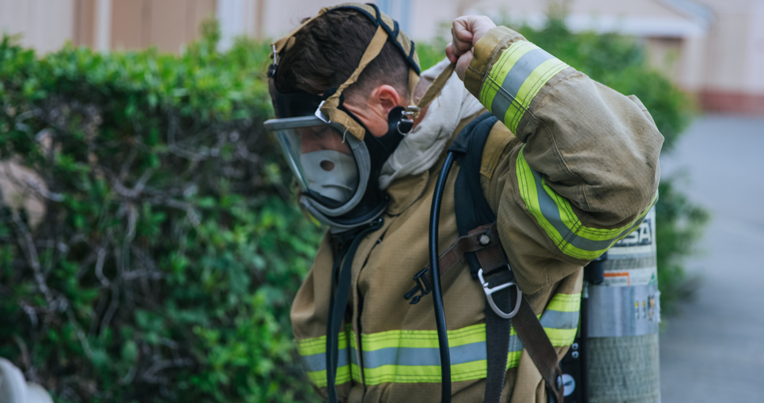 Student securing firefighting mask on face
