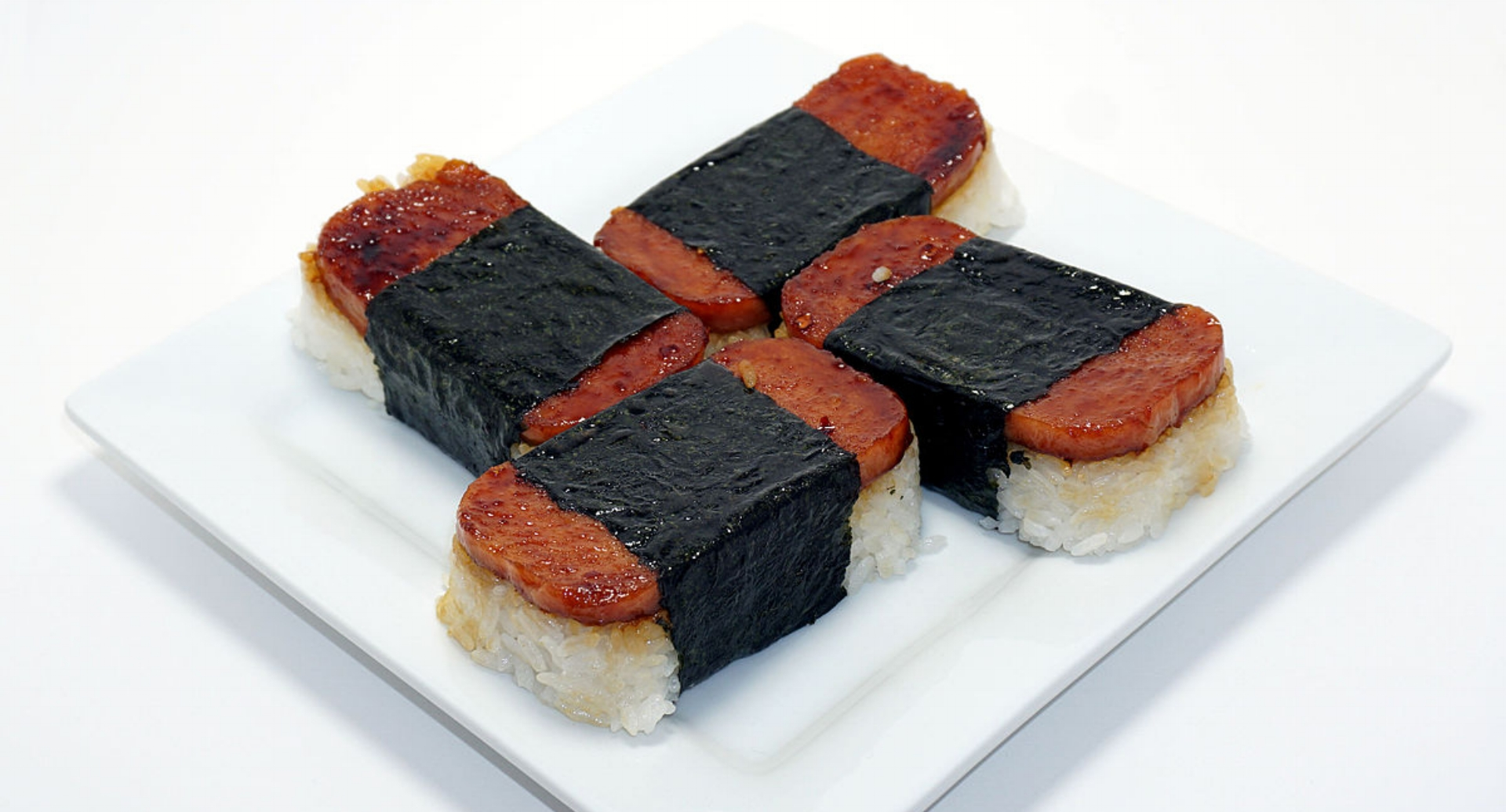 SPAM MUSUBI   a popular snack and lunch food in Hawaii composed of a slice of grilled Spam on top of a block of rice, wrapped together with nori in the tradition of Japanese  omusubi