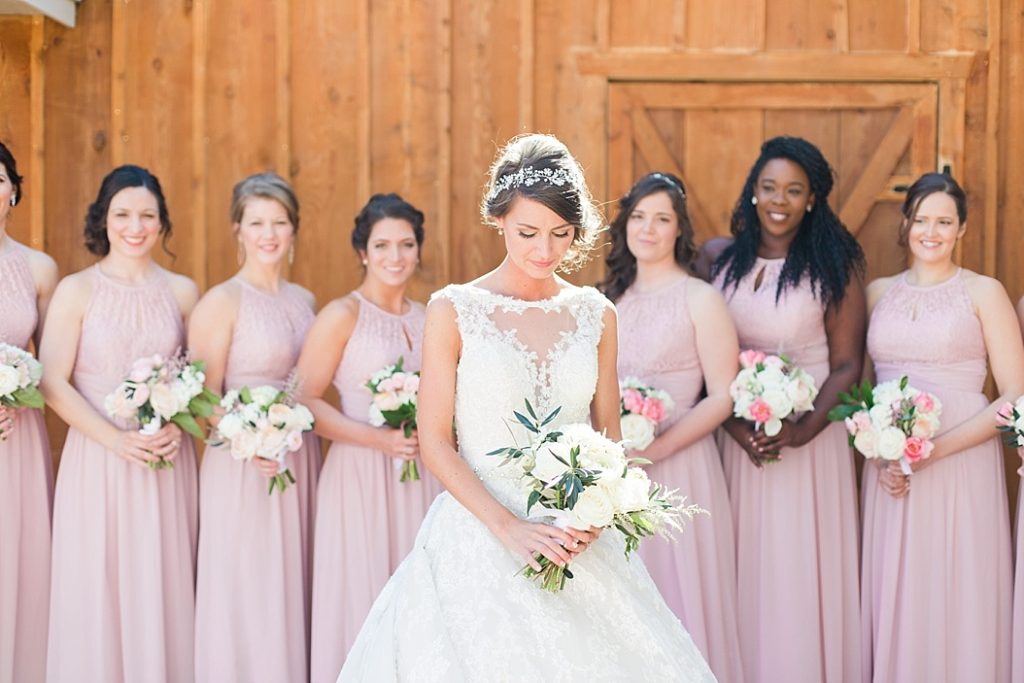 Amylynn selected a palate of pinks and whites, with a request for a white bouquet. We selected a combo of gorgeous ranunculus, garden roses, astilbe and scabiosa with olive leaves for an accent. Pops of color were added to the bridesmaids bouquets with amazing double tulips and pink ranunculus.  One thing I love to do with my brides is design every element of their wedding around their desired look, so we also created custom invitations and programs with a logo designed especially for her!