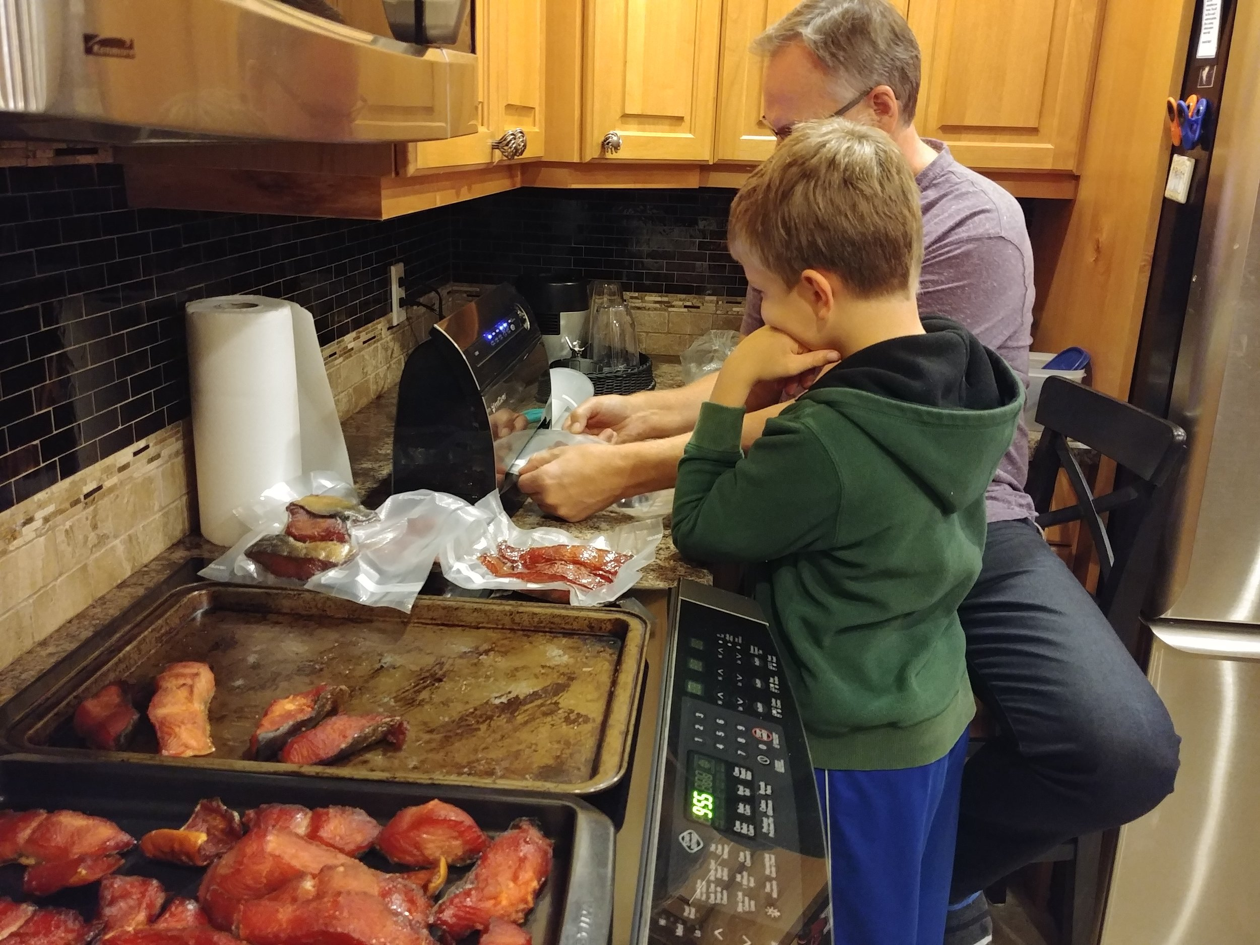 Sid vacuum-packing the salmon Jer caught and Sid smoked…