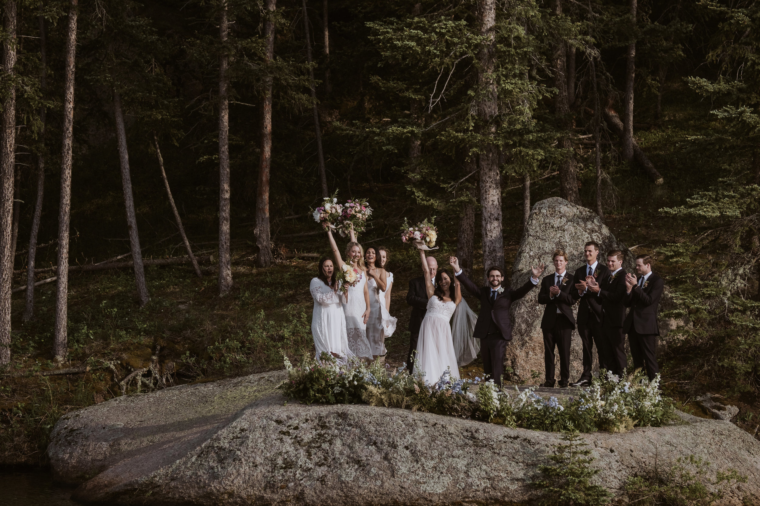A nest of wildflowers, foliage, and grasses surrounds the bridal party.