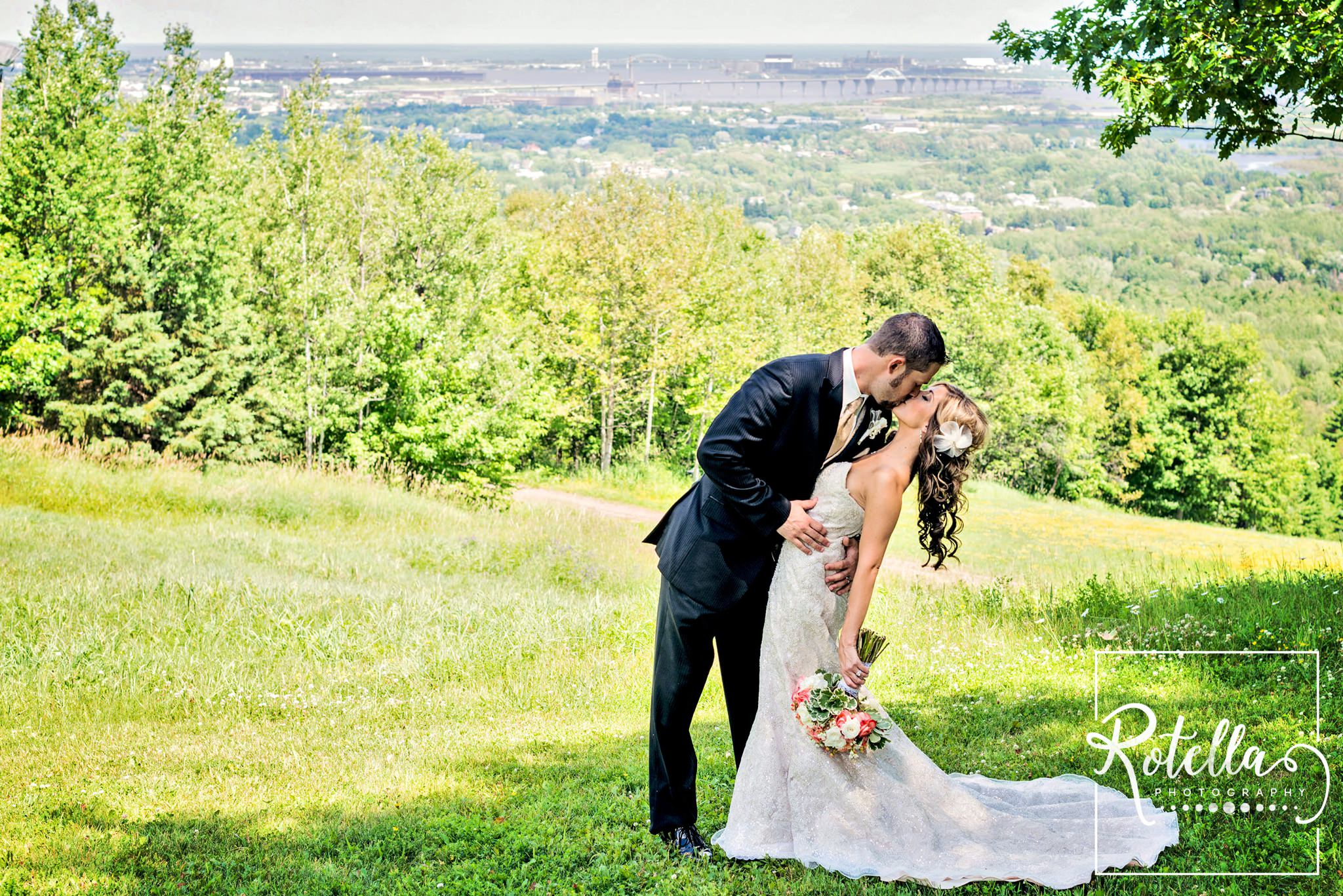 Bride and groom kissing at spirit mountain, duluth
