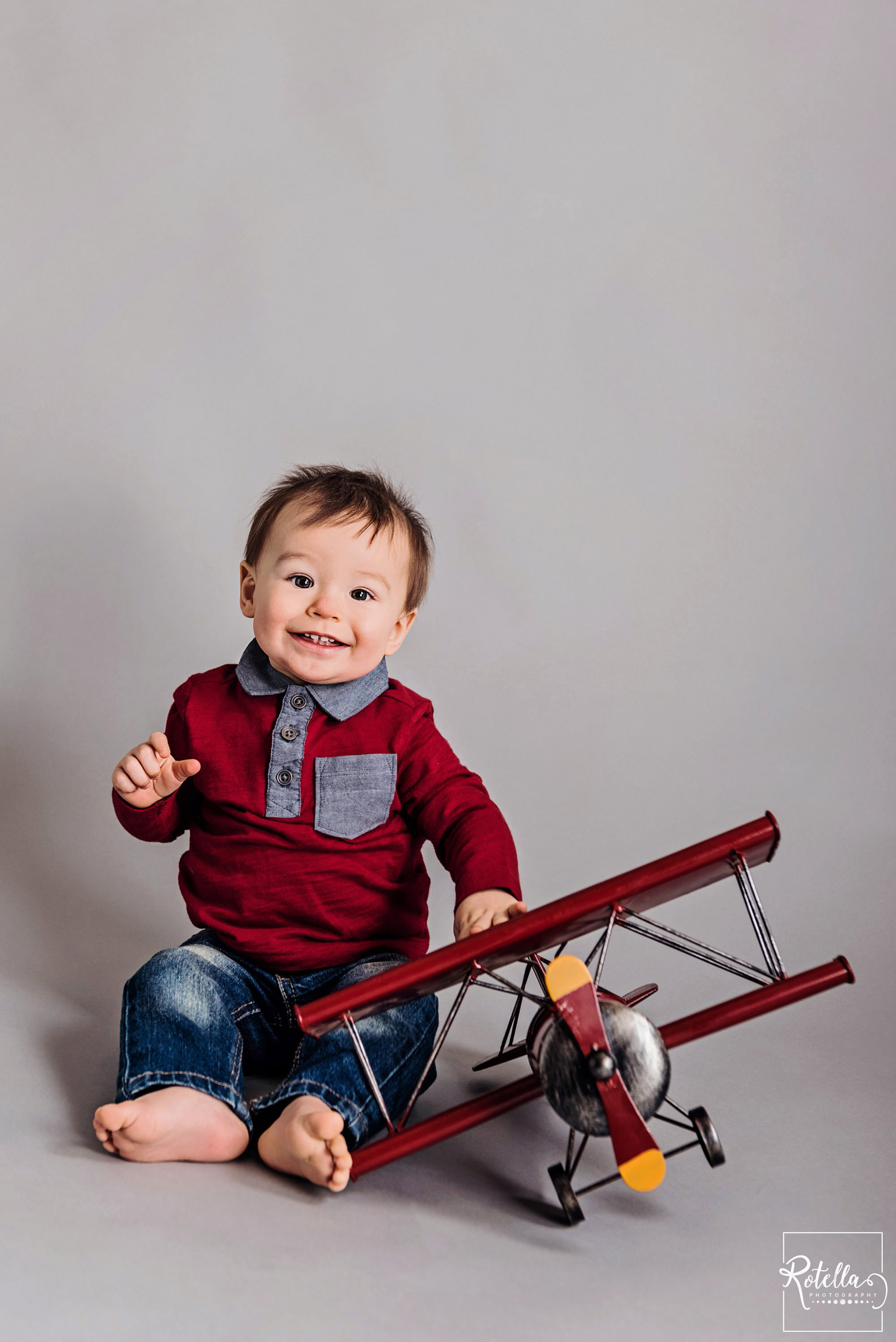 Rotella Photography - baby playing with red plane on grey backdrop