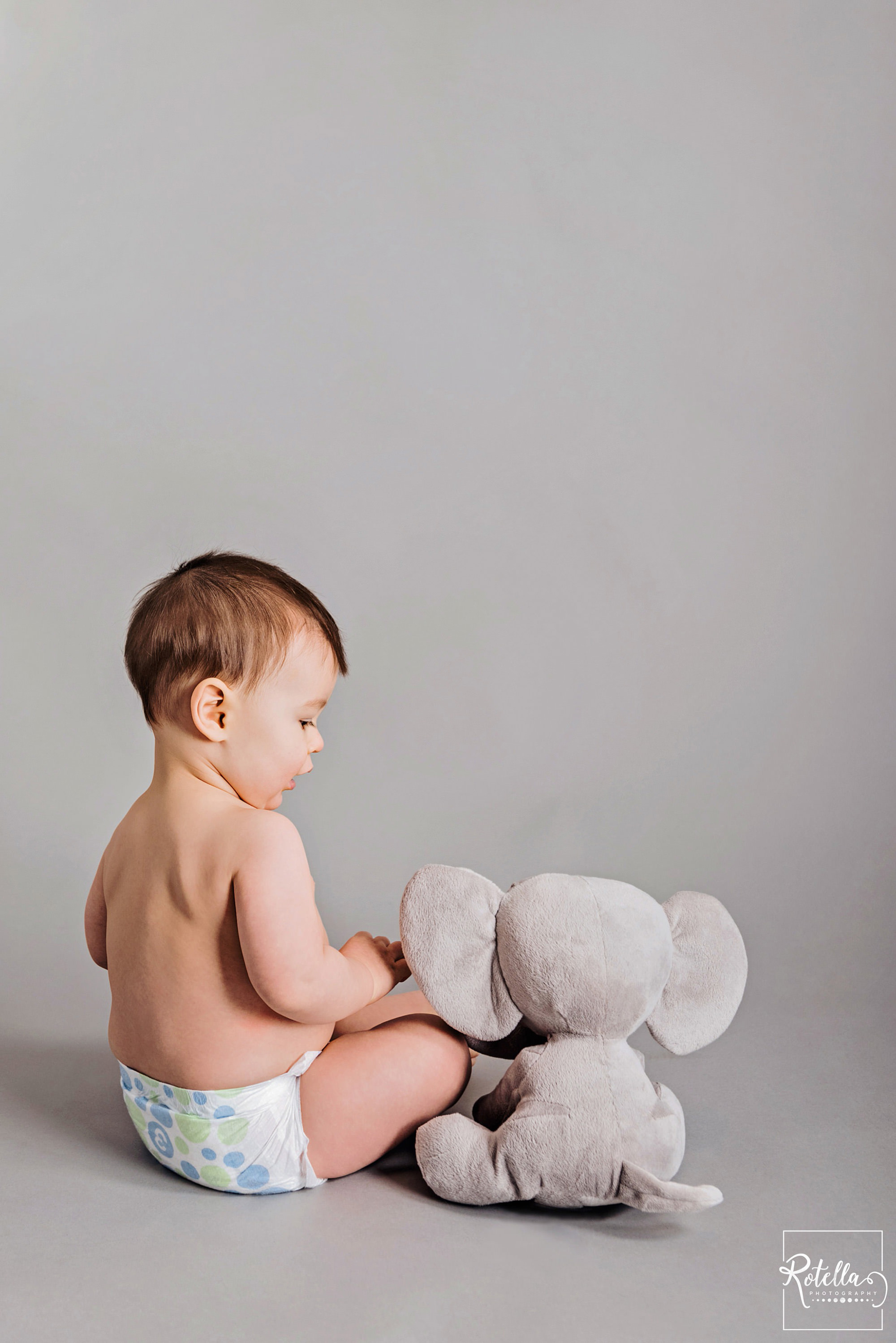 Rotella Photography - milestone photography baby playing with stuffed elephant in studio on grey backdrop