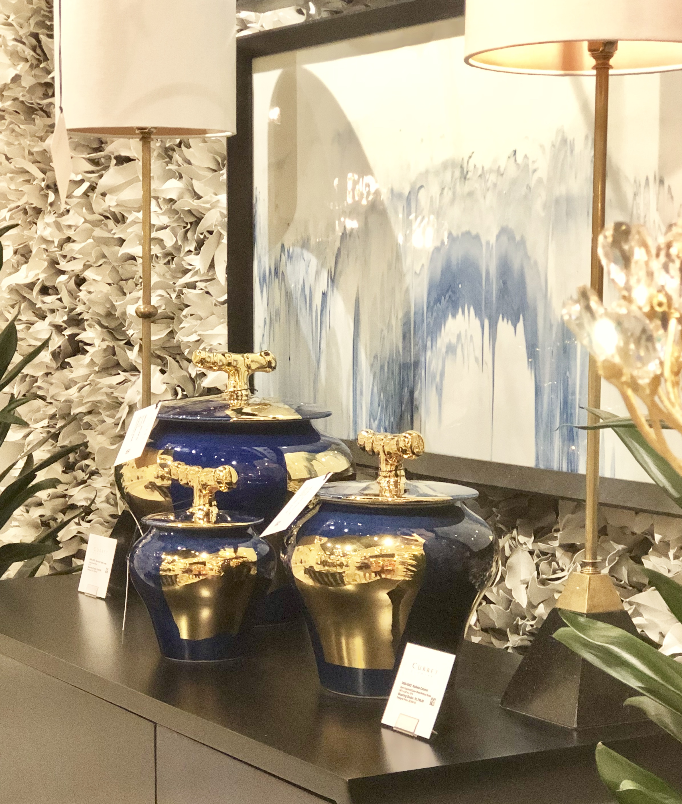 First, check out the canvas in the back—painted, loose, dripping hues. Then, notice the jars—deep blues with brush strokes of gold with a very large handle.