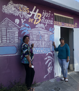 Josefina Pacheco (left) and her sister in front of the Belgica community center being refurbished.